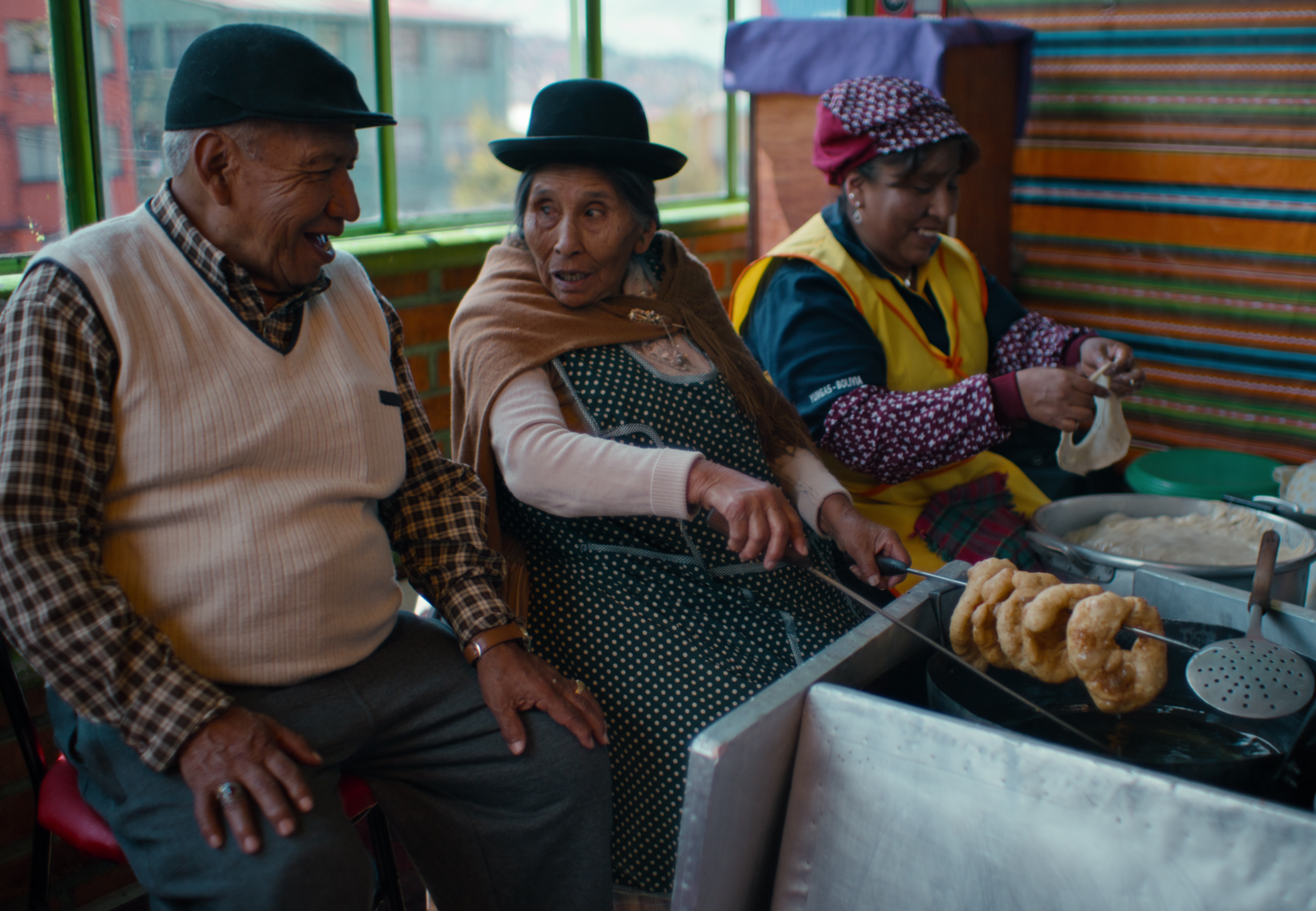 In Bolivia, an elderly man in a white sweater vest and black cap chats with two women in aprons as they prepare and fry dough in a room decorated in bright colored blankets.