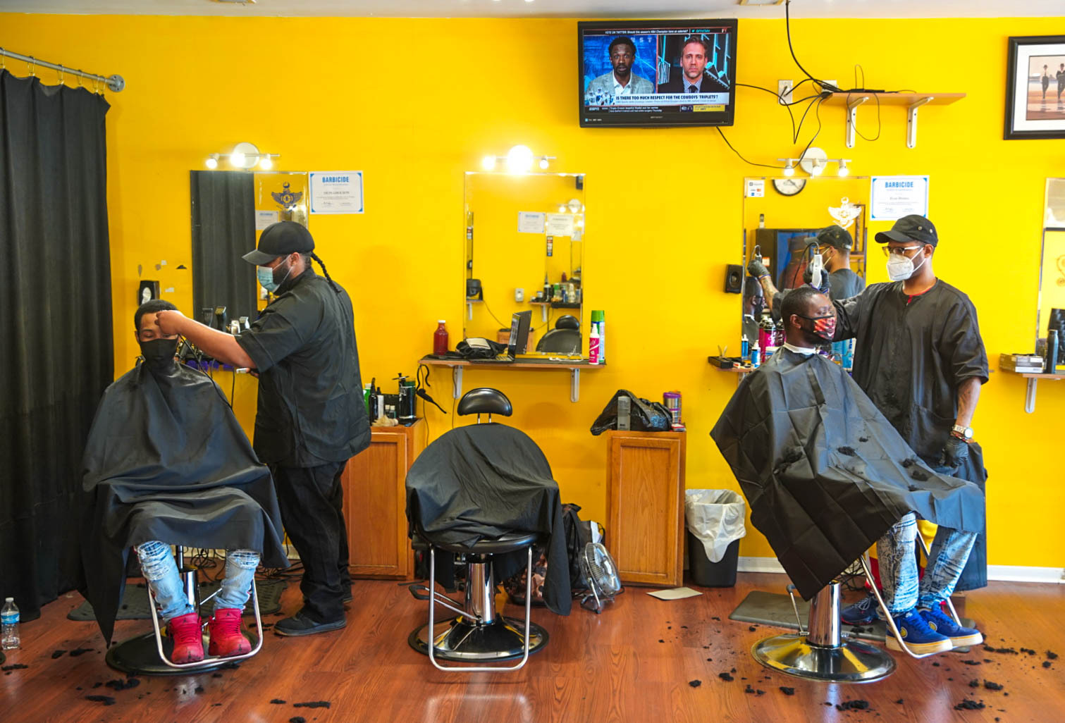 Two young men sit a socially distanced two barber chairs apart as they get haircuts Friday at newly reopened C'Styles Barber Shop in Markham.