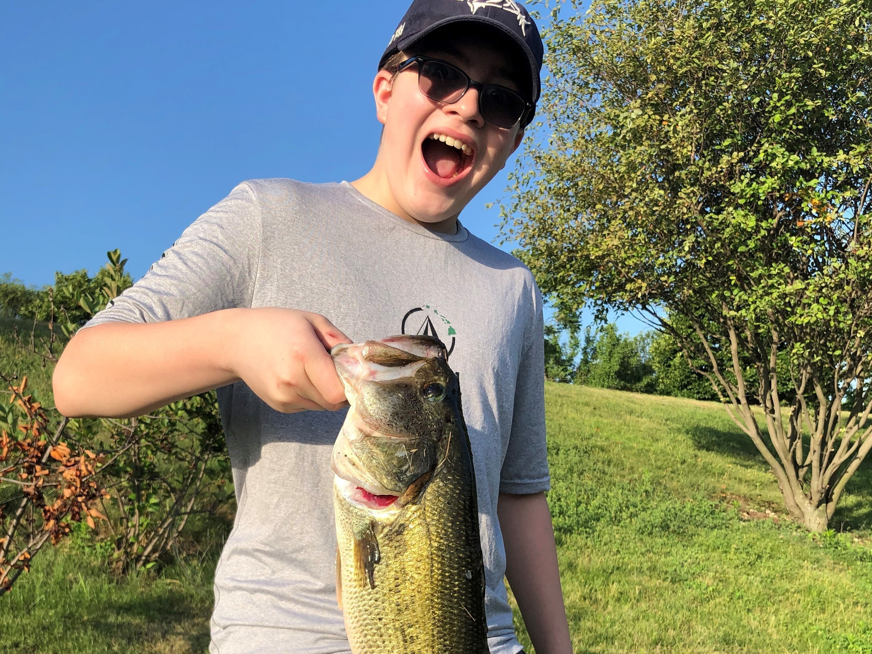 A.J. Koenigsknecht catches the joy of fishing while hoisting the largemouth bass he caught last weekend on a family excursion. Photo provided