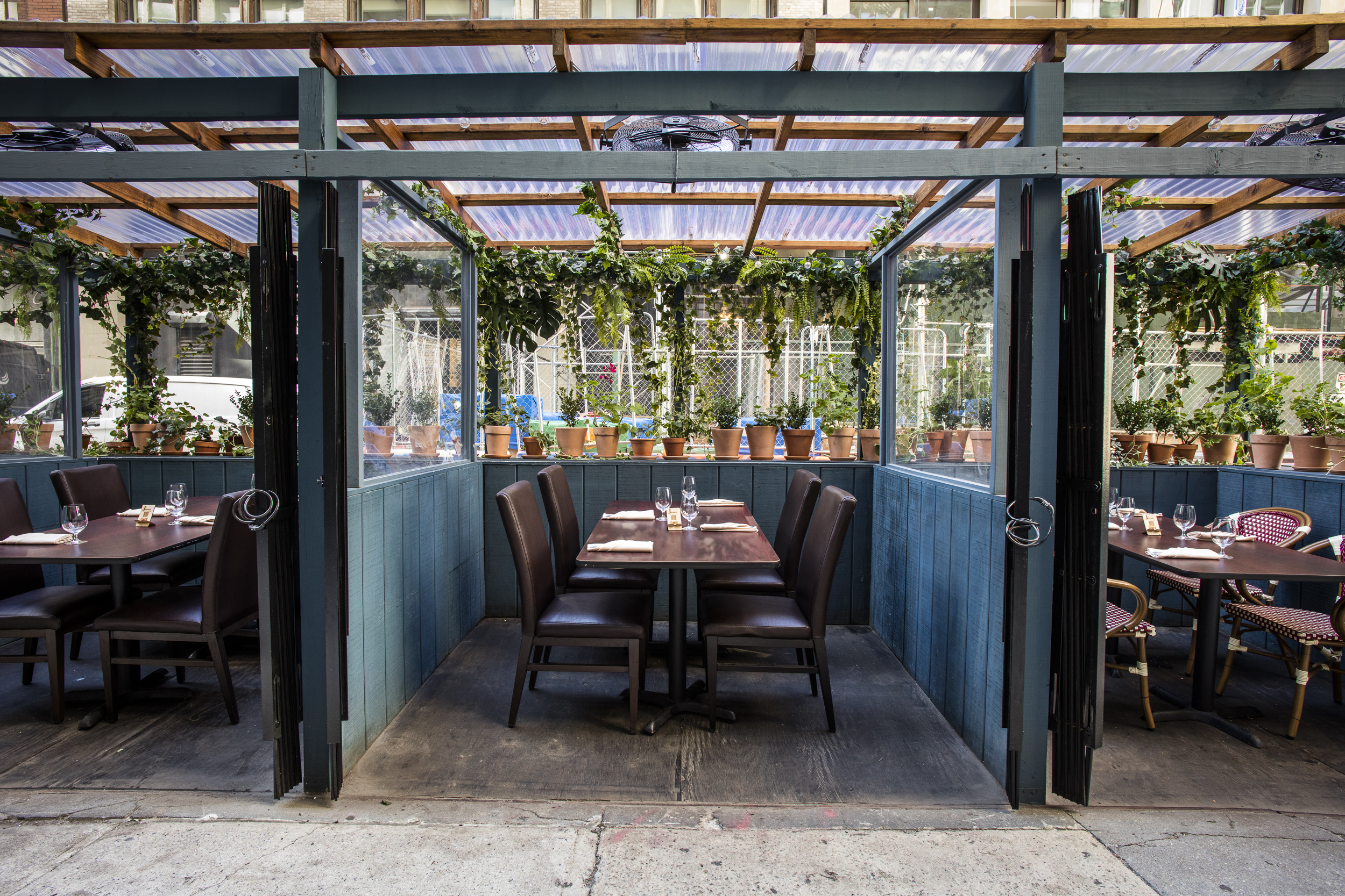 A covered outdoor structure at Jonoon, complete with tables and chairs set for service and hanging plants.