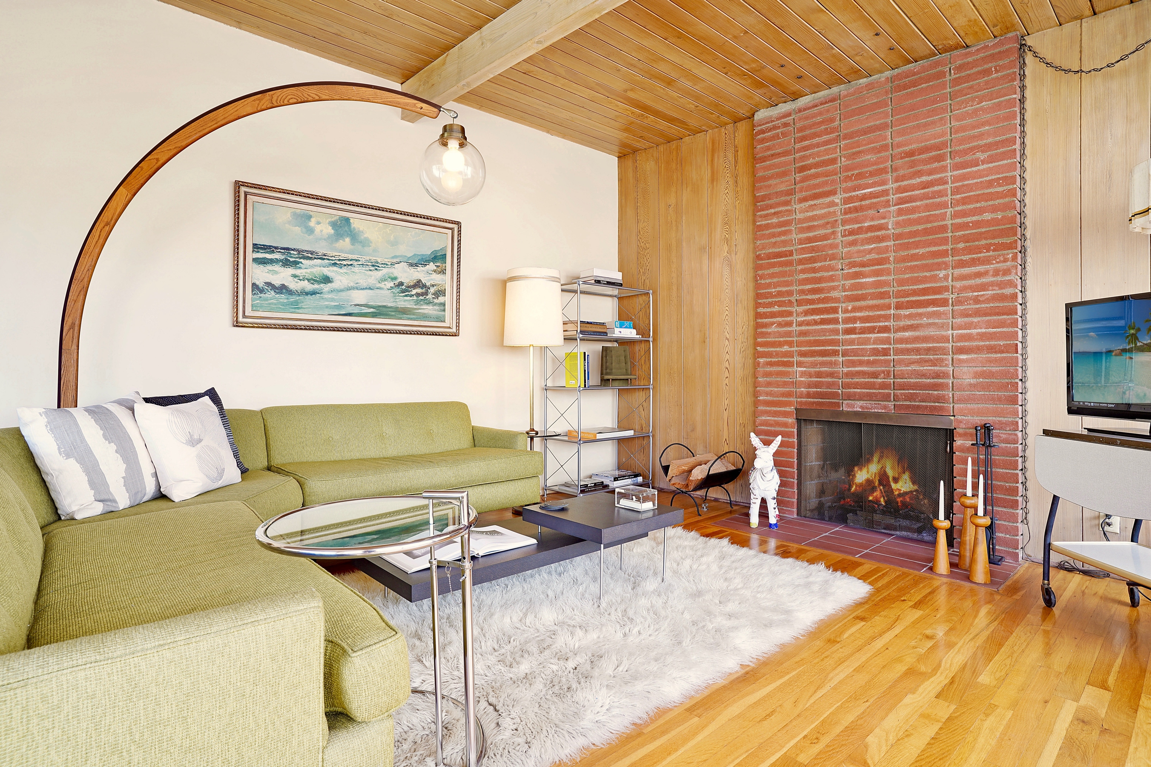 Living room with light wood floors and full-height brick fireplace.