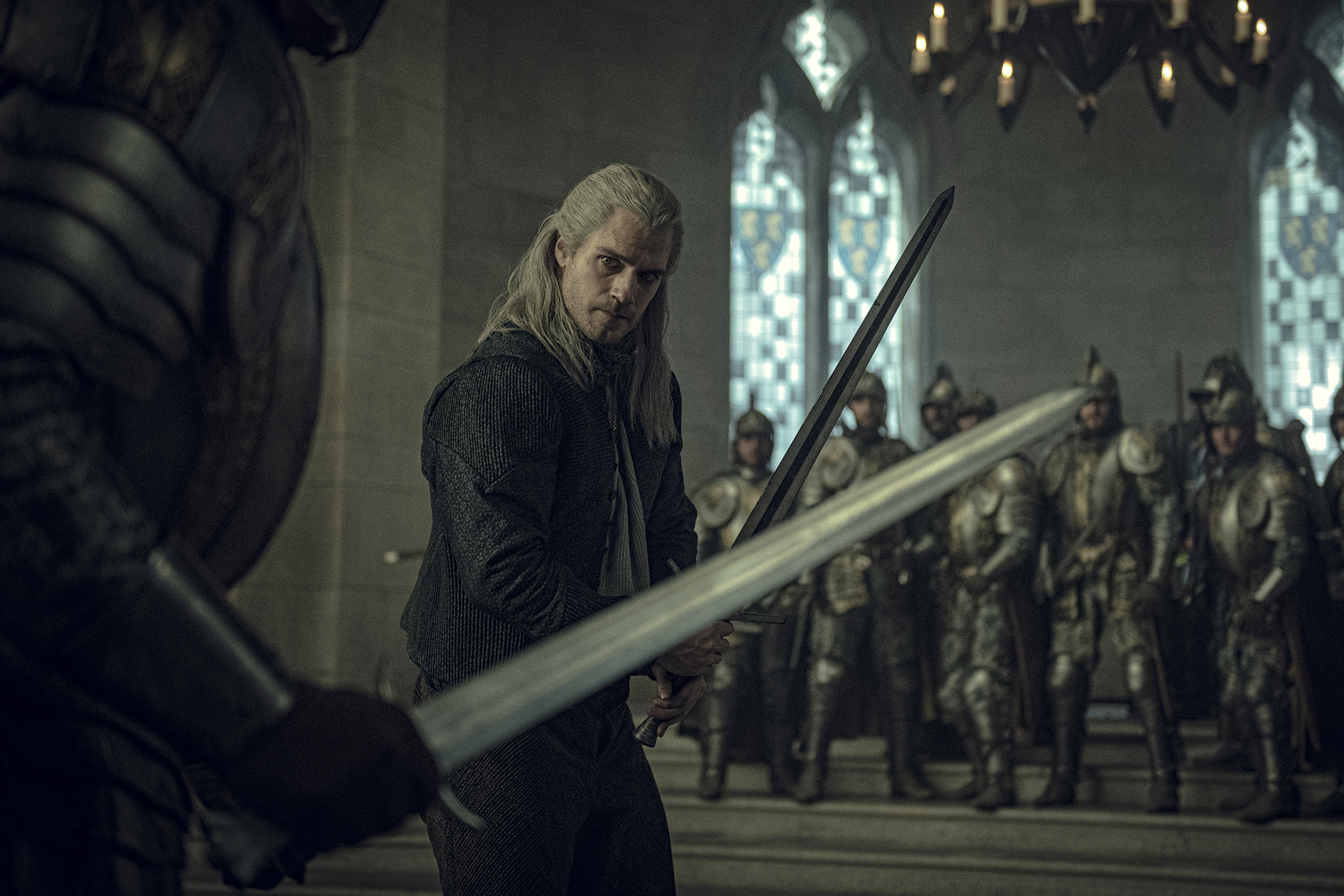 Henry Cavill as Geralt of Rivia squares up on an armored knight in The Witcher on Netflix.
