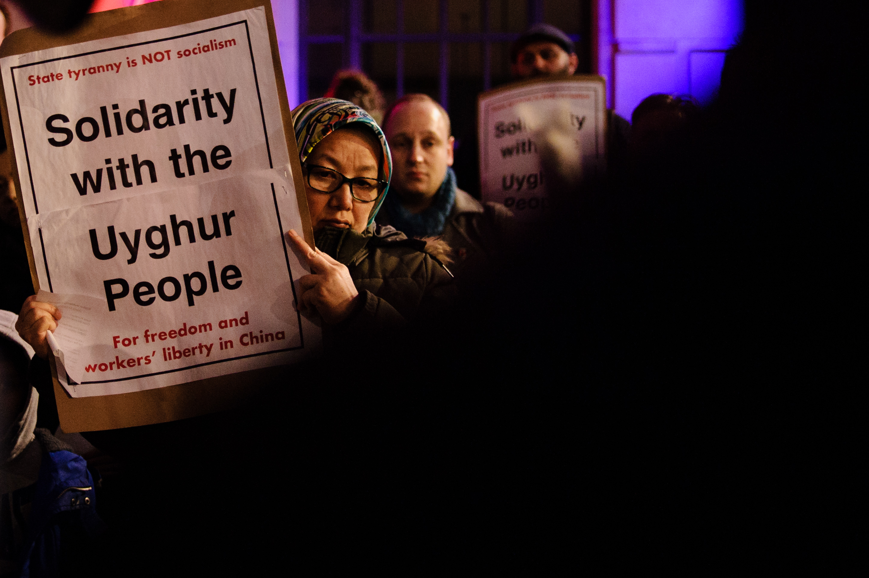 """A protester holds a sign that reads """"Solidarity with the Uyghur people."""""""