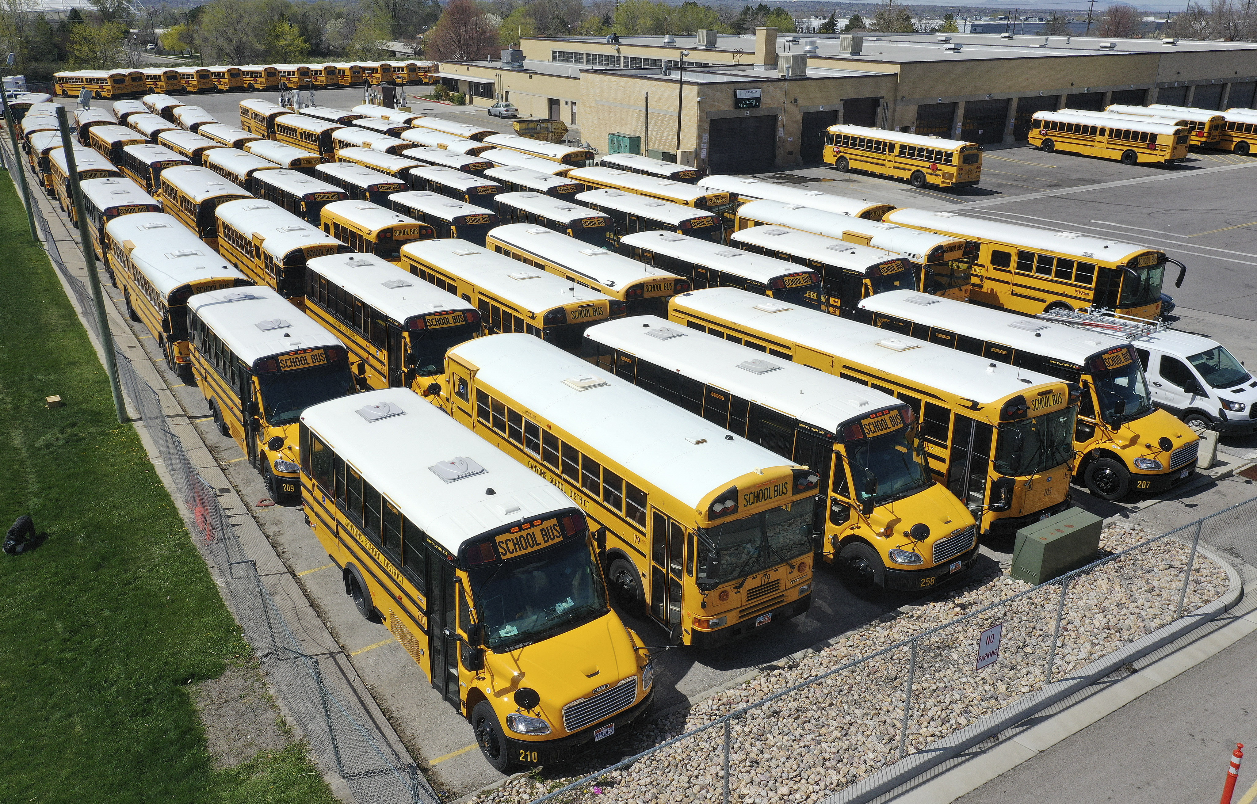 Canyons School District buses sit idle in a parking lot in Sandy on Tuesday, April 14, 2020. Utah's K-12 public schools will remain closed for in-person learning for the remainder of the academic year, state officials announced Tuesday.