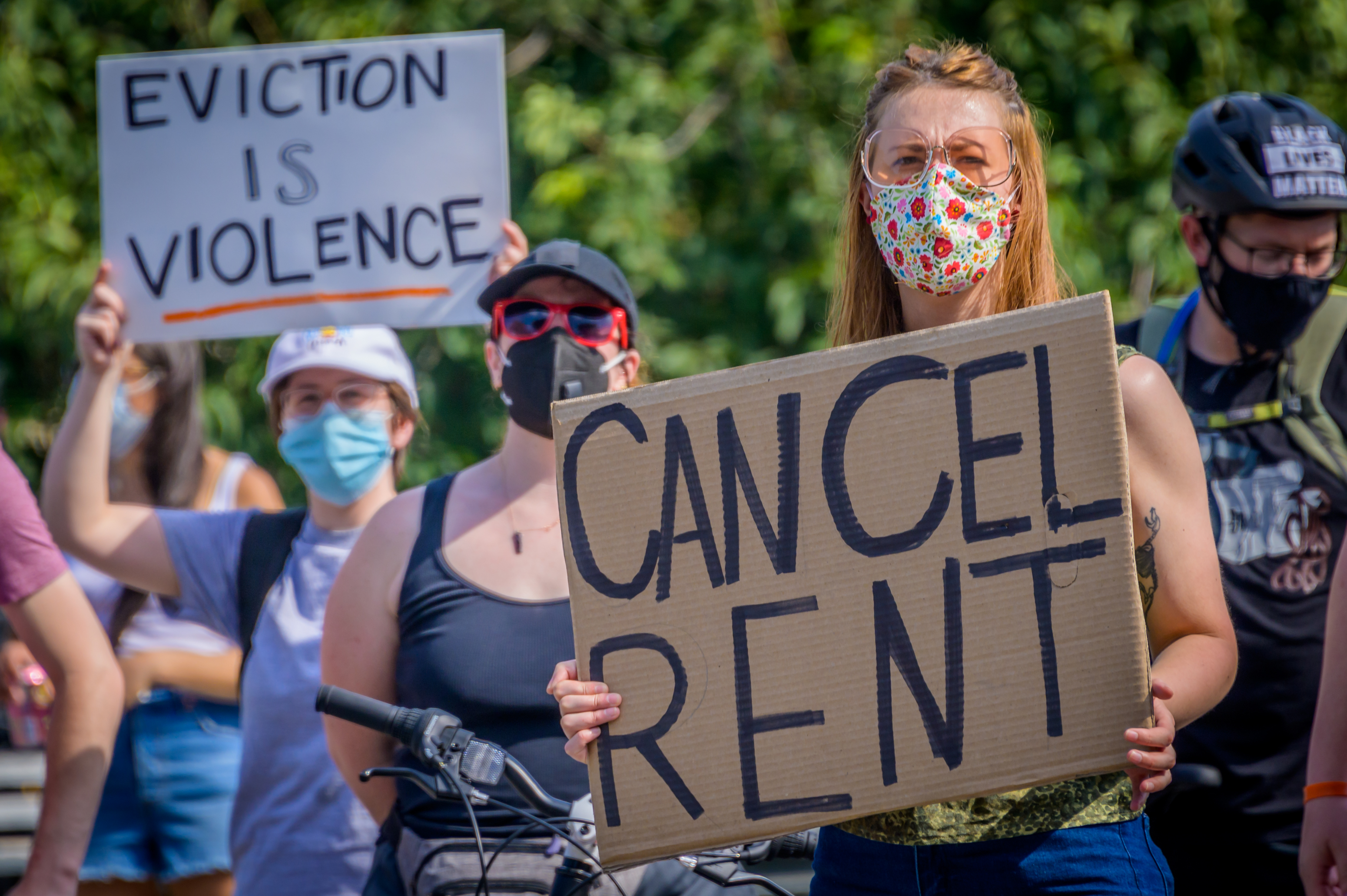 """Two protestors hold signs that read, """"Cancel Rent"""" and """"Eviction Is Violence"""" at a protest in Brooklyn."""