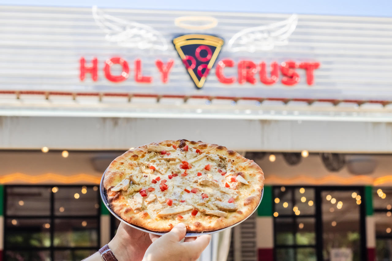 """a pair of hands holding a whole pizza in front of a neon sign that says """"holy crust"""""""
