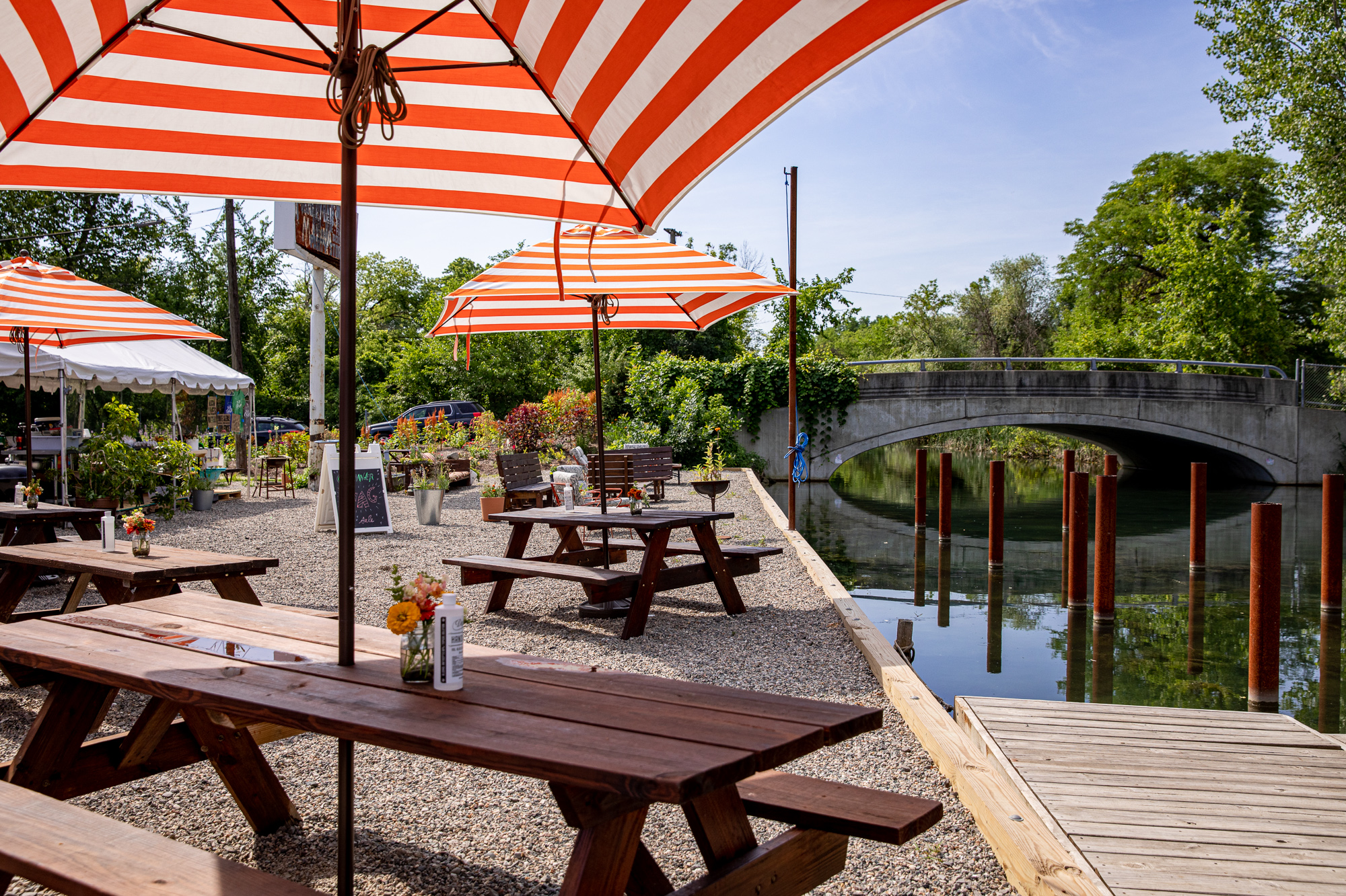 Orange and white striped umbrellas cover wooden picnic tables with orange flowers in vases and bottles of hand sanitizer next to a dock.