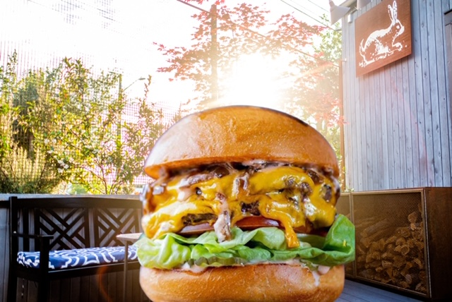 A composite photo of the wagyu burger from Tarsan i Jane's XITA pop-up against the backdrop of the restaurant itself