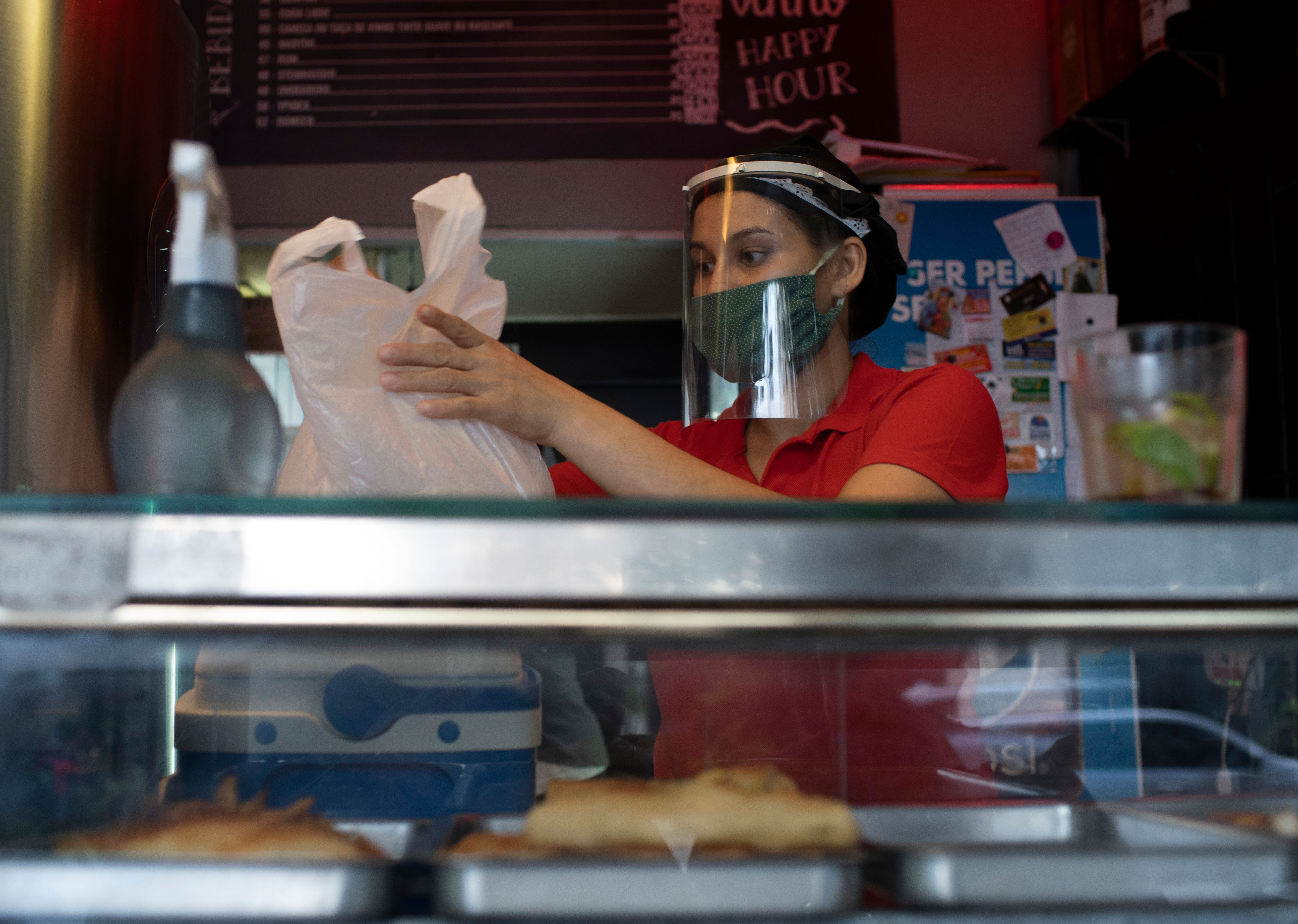 Woman wearing face mask and face shield preparing plastic bag of food from behind a counter.