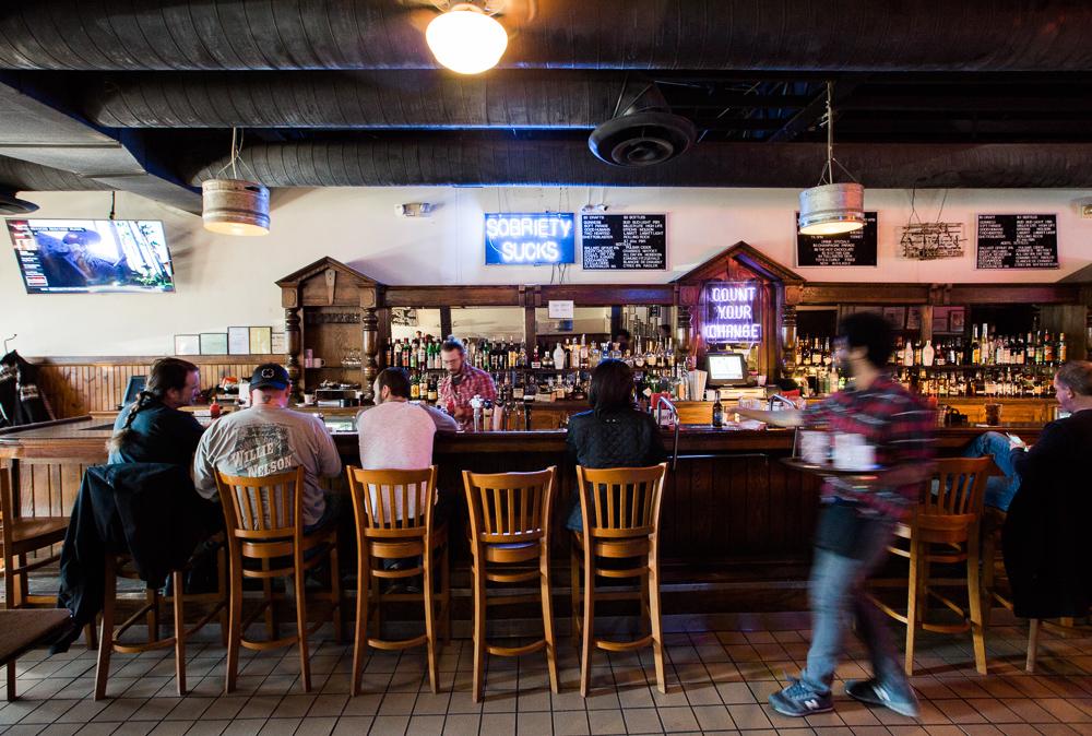 A sig reading sobriety sucks hangs behind a full bar at Honest John's.