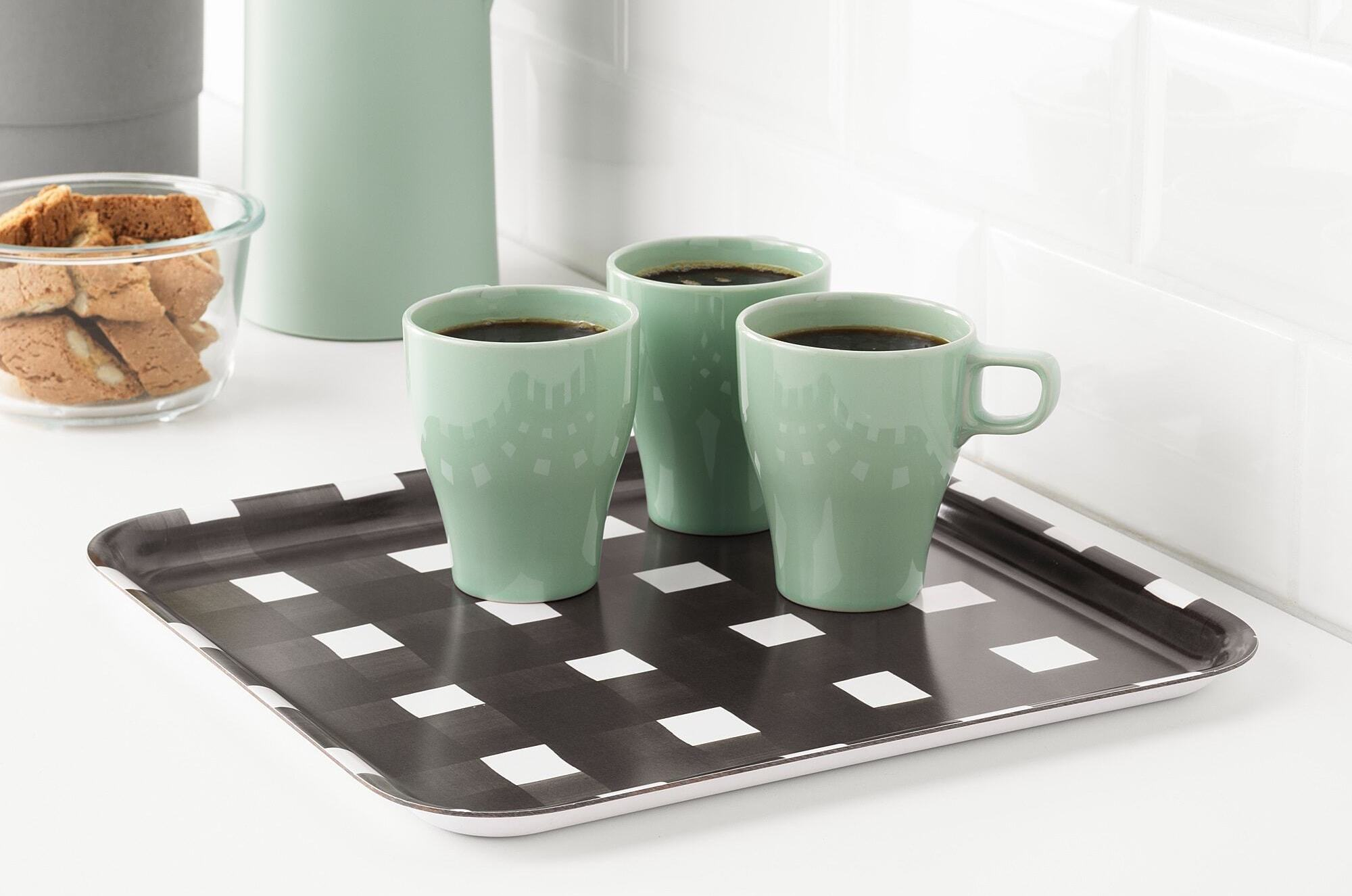 A black and white tray with three cups of coffee