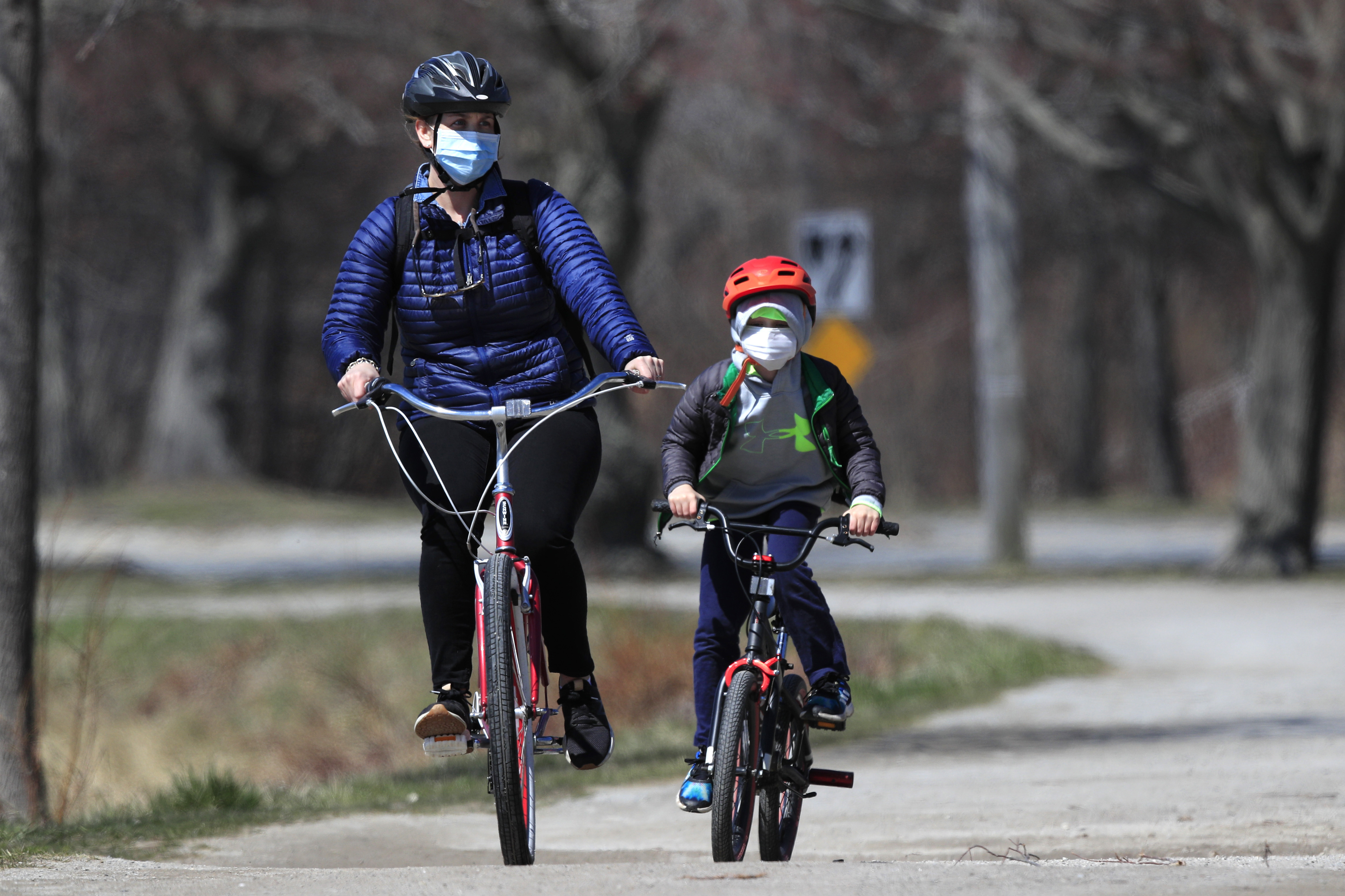 In this Wednesday, April 8, 2020, photo, bicyclists wear pandemic masks while riding in Portland, Maine. Bicycle sales have surged as shut-in families try to find a way to keep kids active at a time of lockdowns and stay-at-home orders during the coronavirus pandemic.