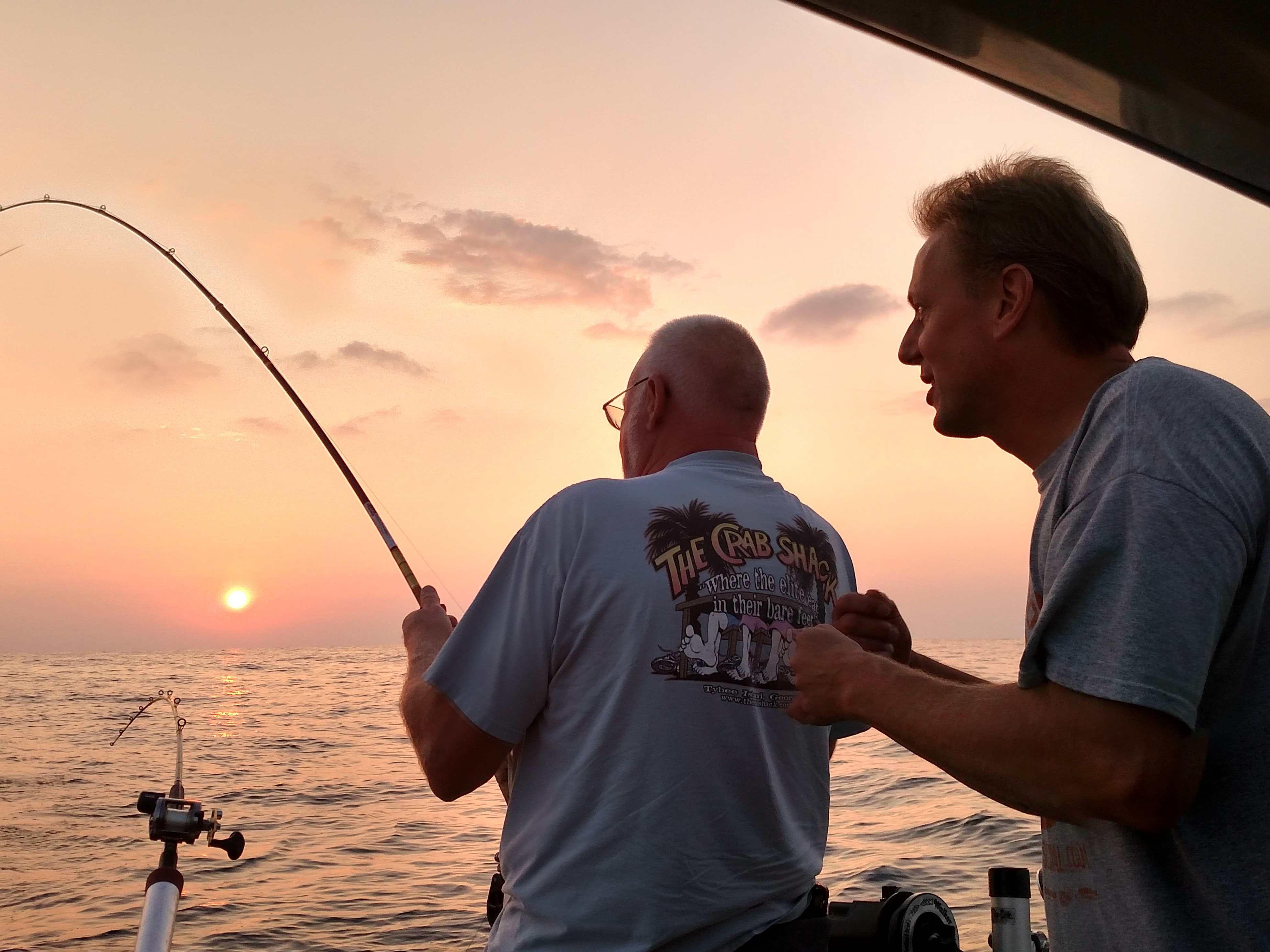 Andy Mikos (right) pleads for a Chinook, such is the draw of kings on Lake Michigan, at dawn on a late summer outing in a file photo. Credit: Dale Bowman