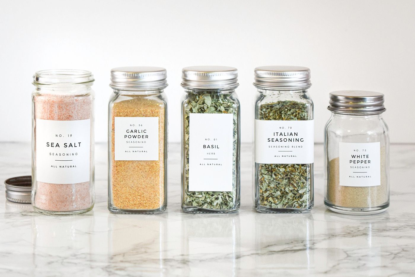 A set of five labeled spice containers in a row