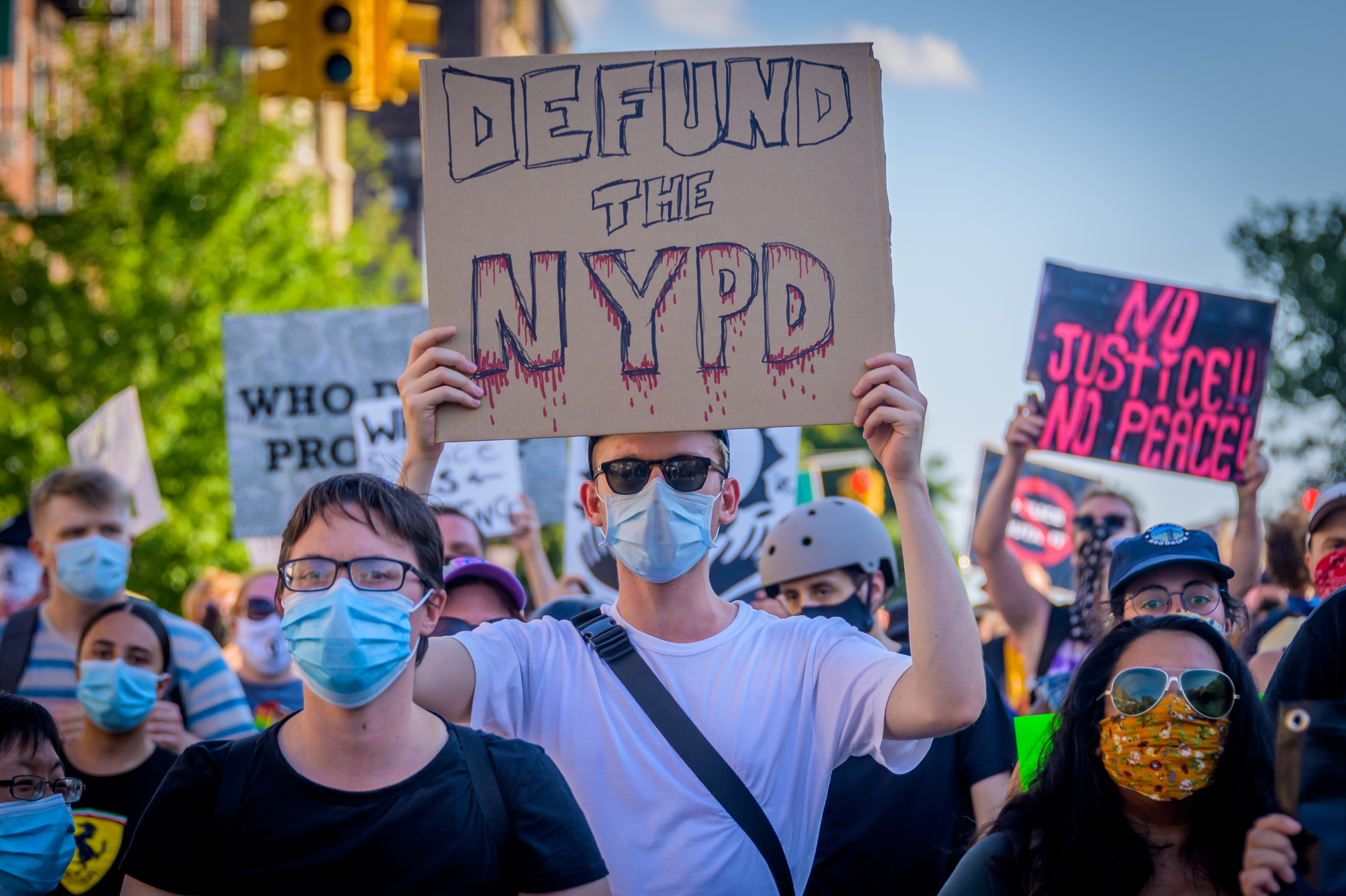 "Protesters hold up signs that read ""Defund the NYPD' and ""No justice, no peace."""