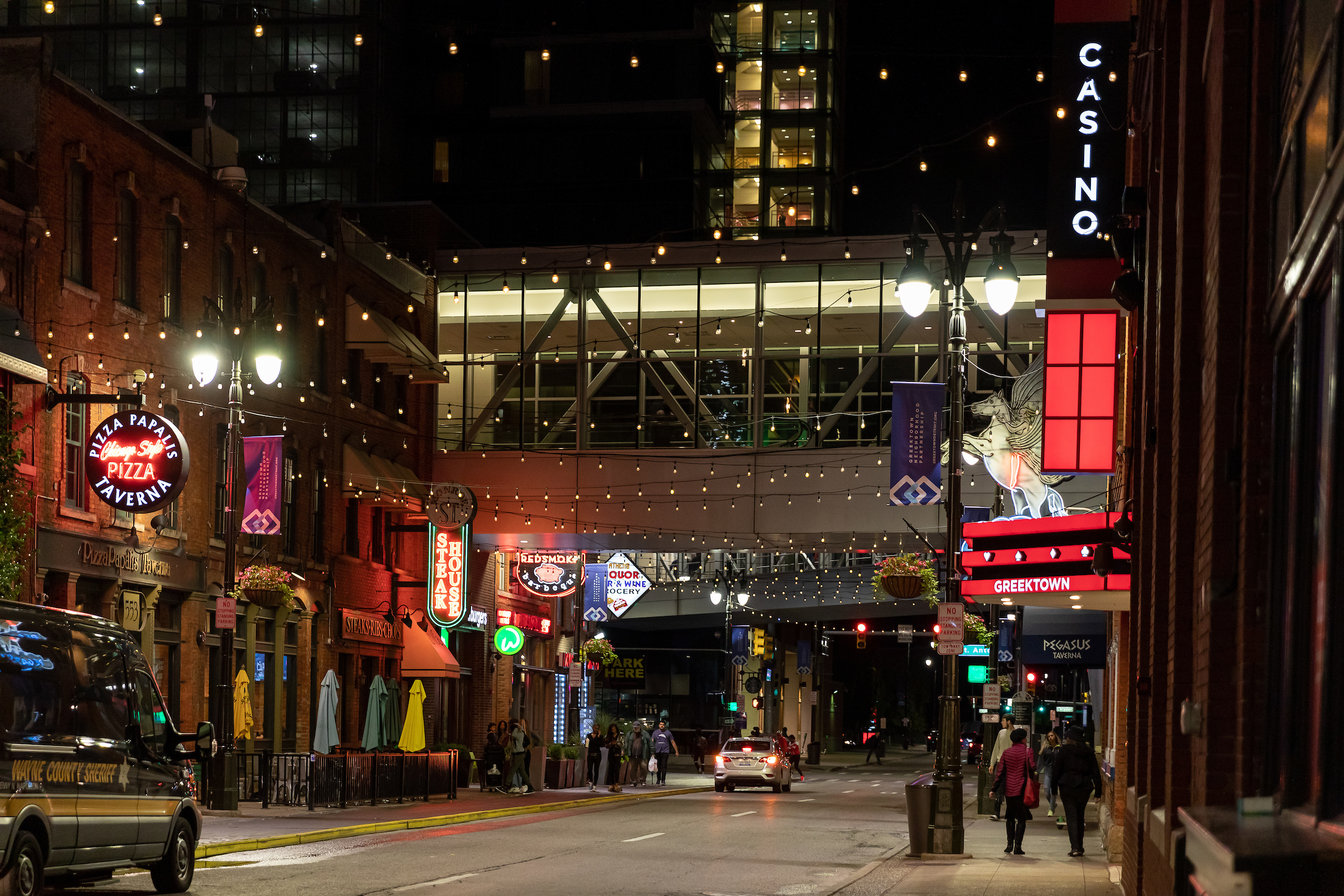 The Greektown entertainment district surrounding the Greektown Casino is shown at night with many restaurant and bar signs lit up and a sky walkway in the background leading to the casino floor.