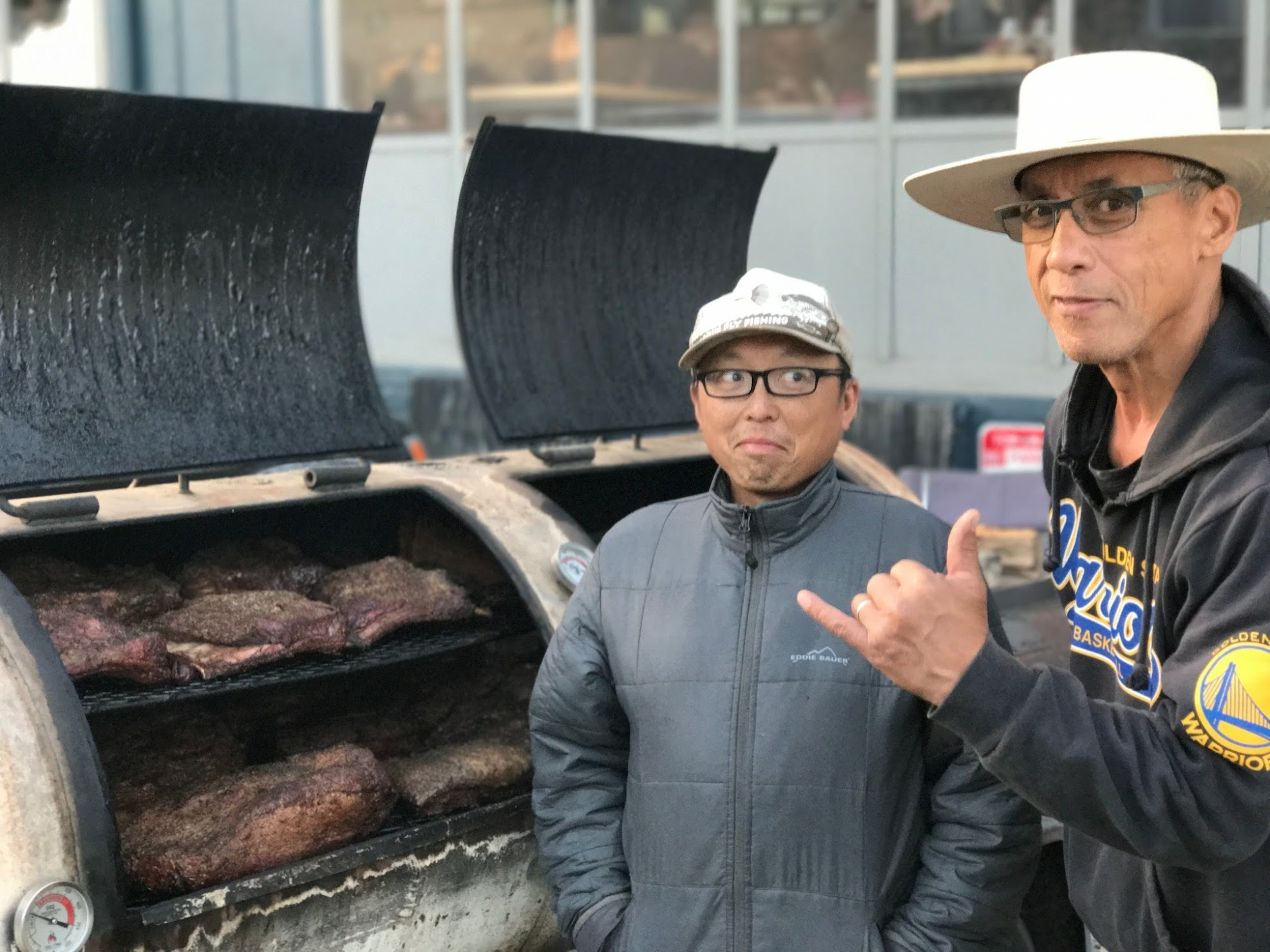 Lau (left) stands in front of a smoker with his friend Harry Pali