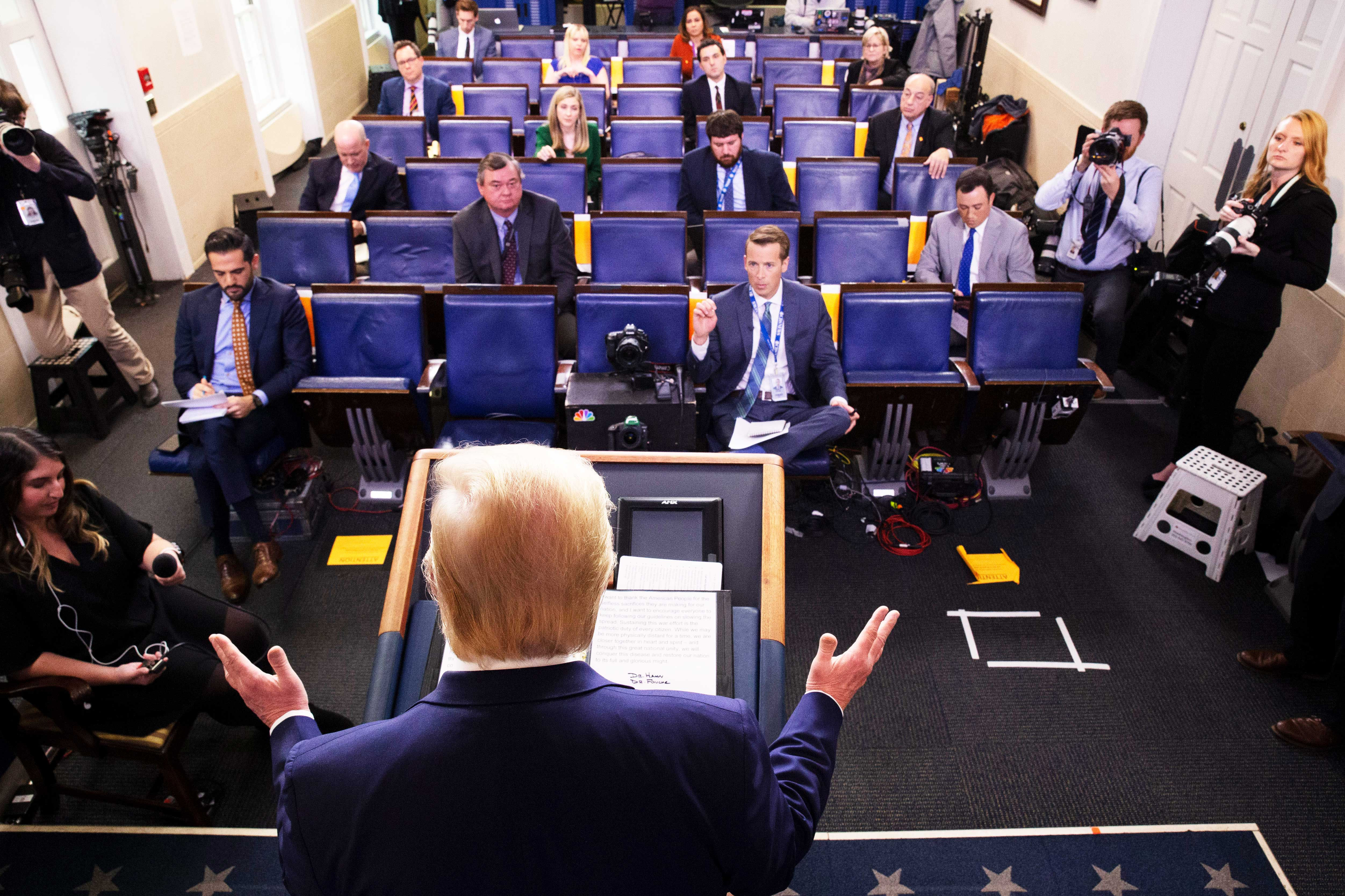 President Trump stands behind a podium while answering questions during a press briefing at the White House.