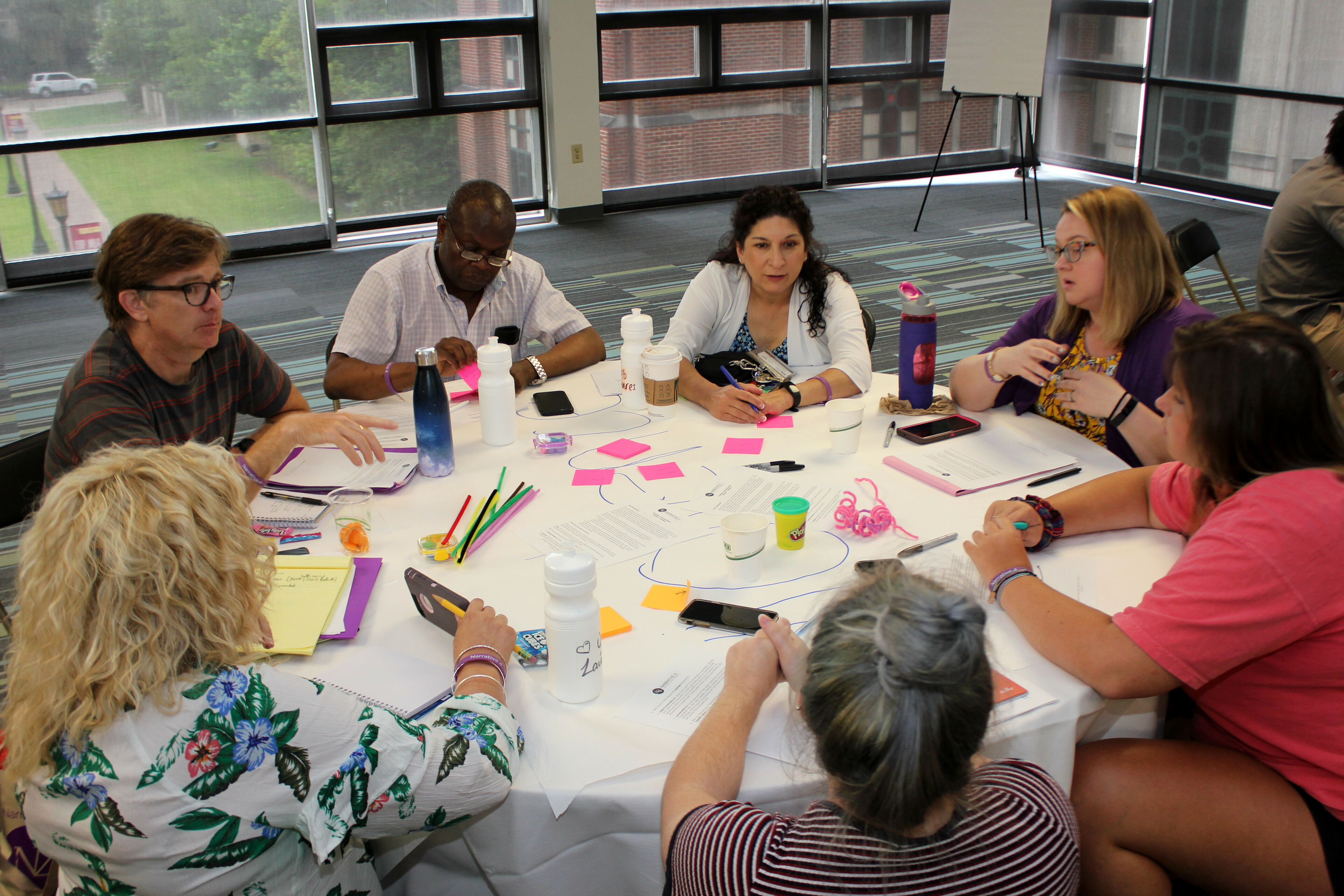 A group of teachers sit at a table and participate in a story exchange