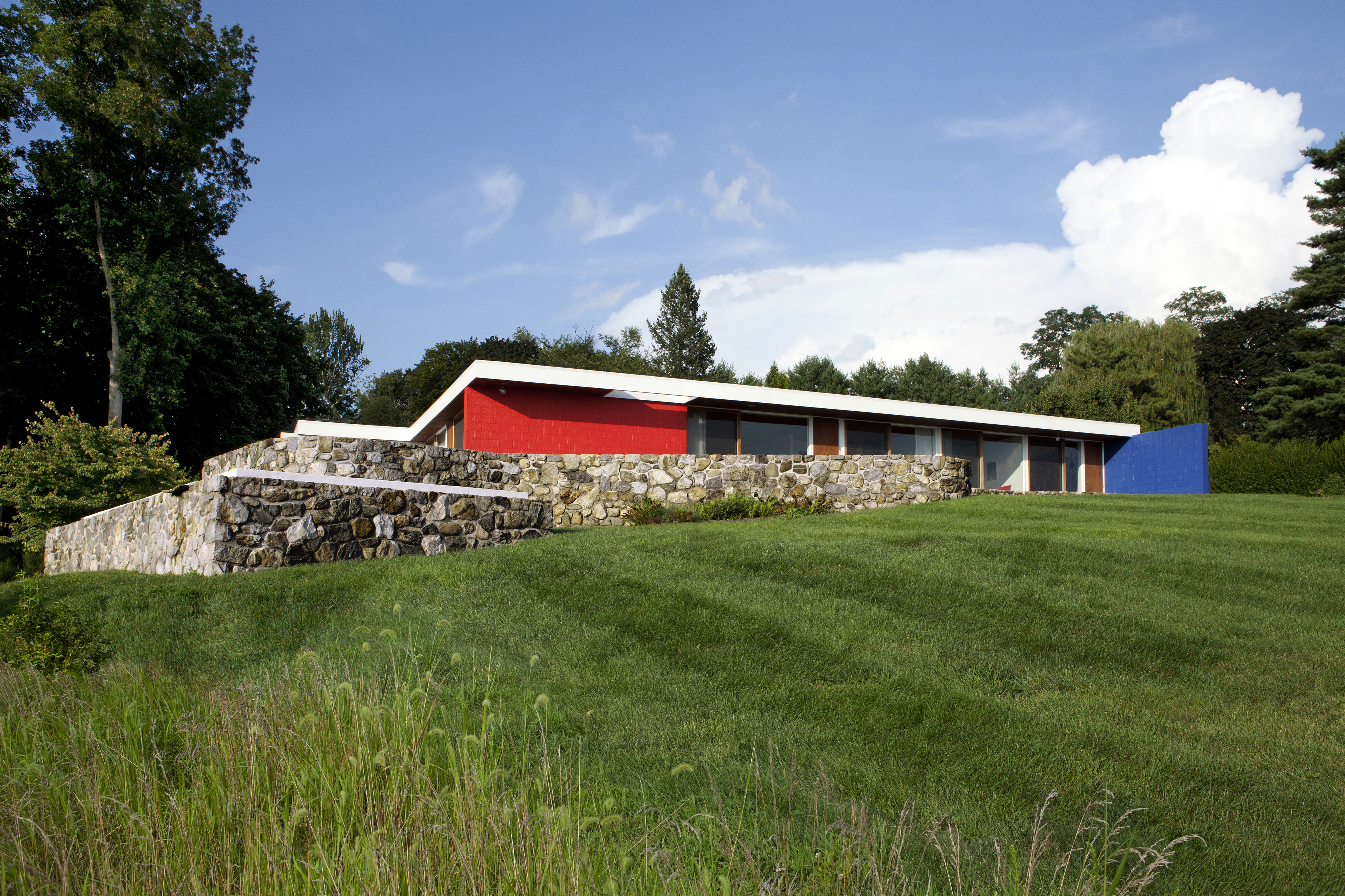 An external view of a stone ranch house designed by Marcel Breuer. There are red and blue walls, white trim, and grass in the front.