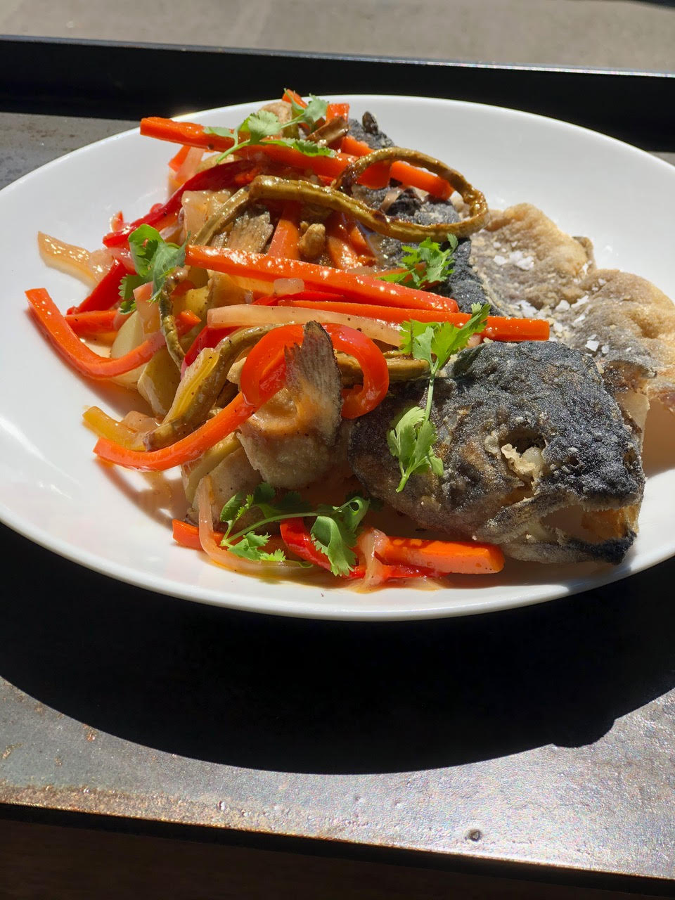 Trout escovitch with pickled peppers, onions, carrots, fiddlehead ferns, and stewed potatoes on a dish at Salare