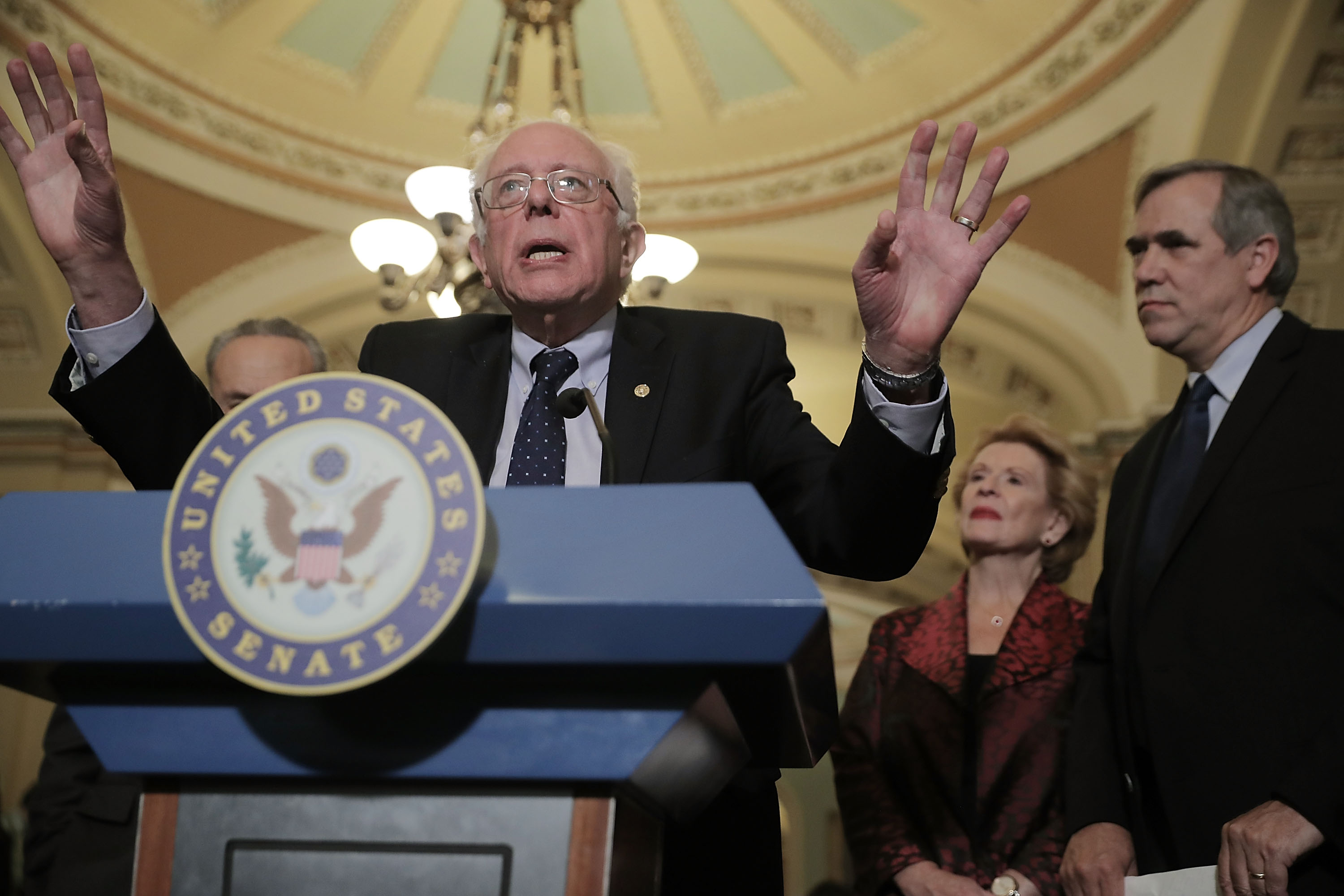 Senator Bernie Sanders speaks from a podium while Senator Jeff Merkley stands to one side listening on October 3, 2017.