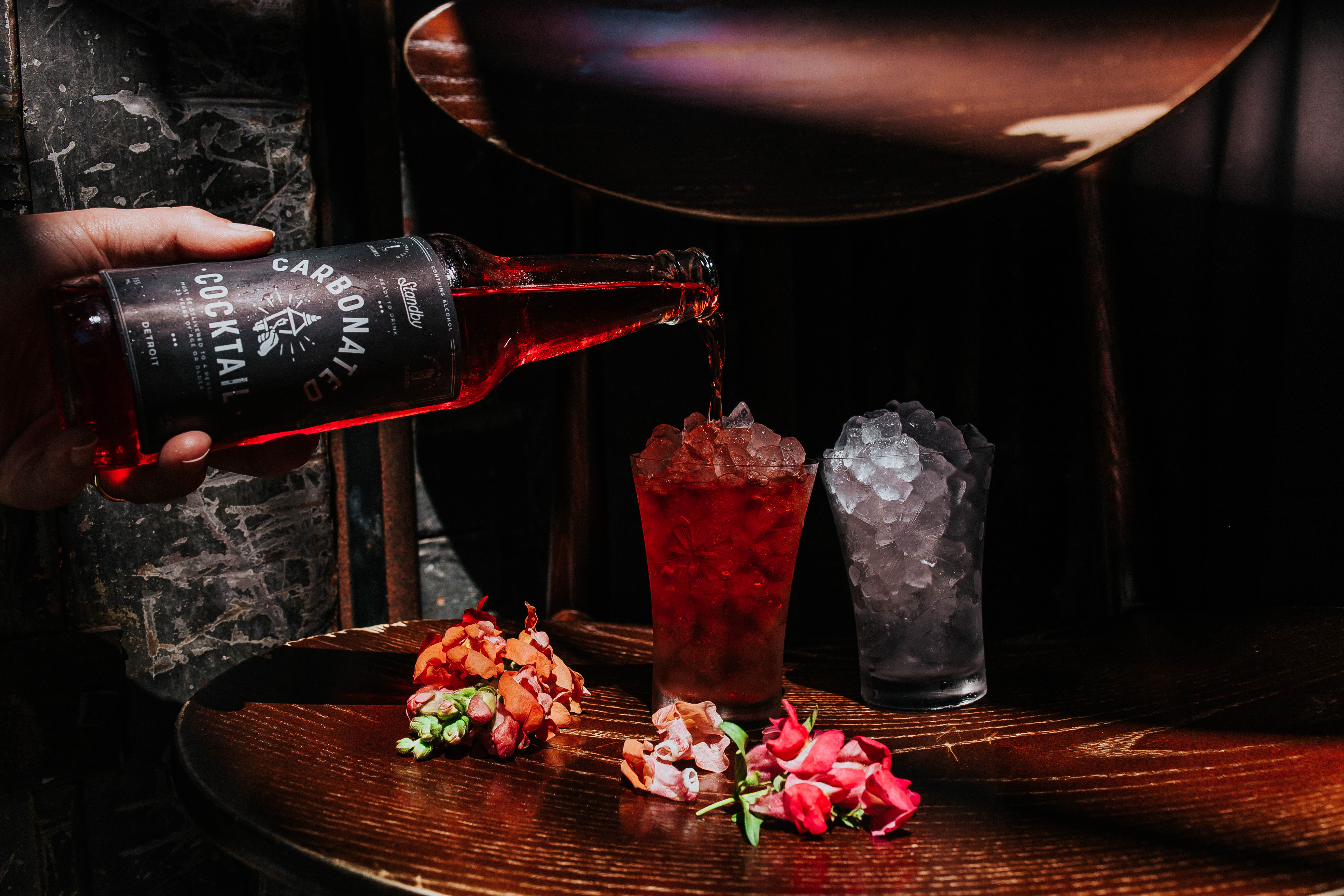 A hand pours a carbonated cocktail from a bottle into a cup of crushed ice next to a second glass of crushed ice with flowers on the table.