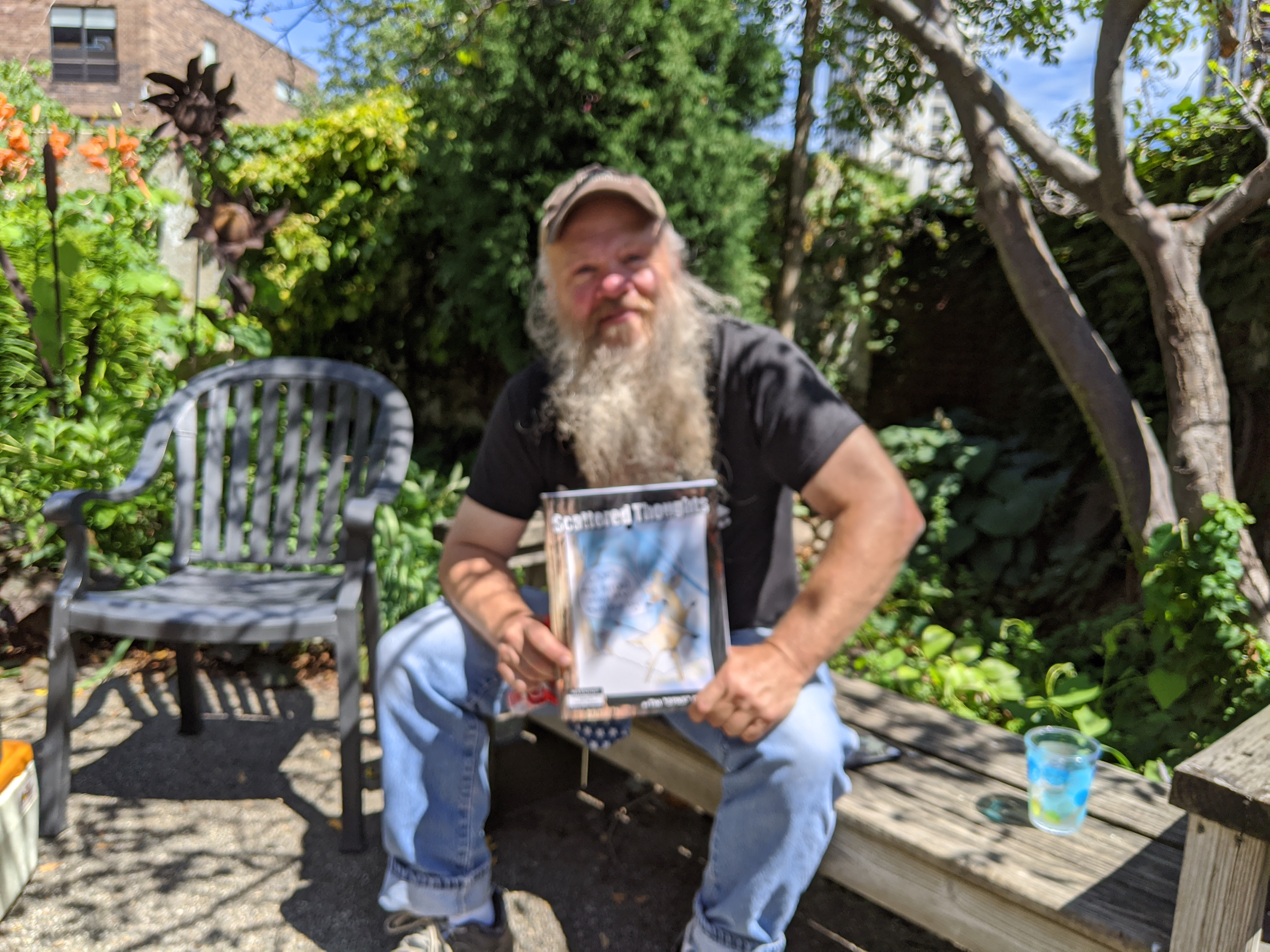 "Tim ""Spike"" Davis poses with his just-released book of cartoons, ""Scattered Thoughts,"" during an interview in a street-side garden in Uptown. Credit: Dale Bowman"