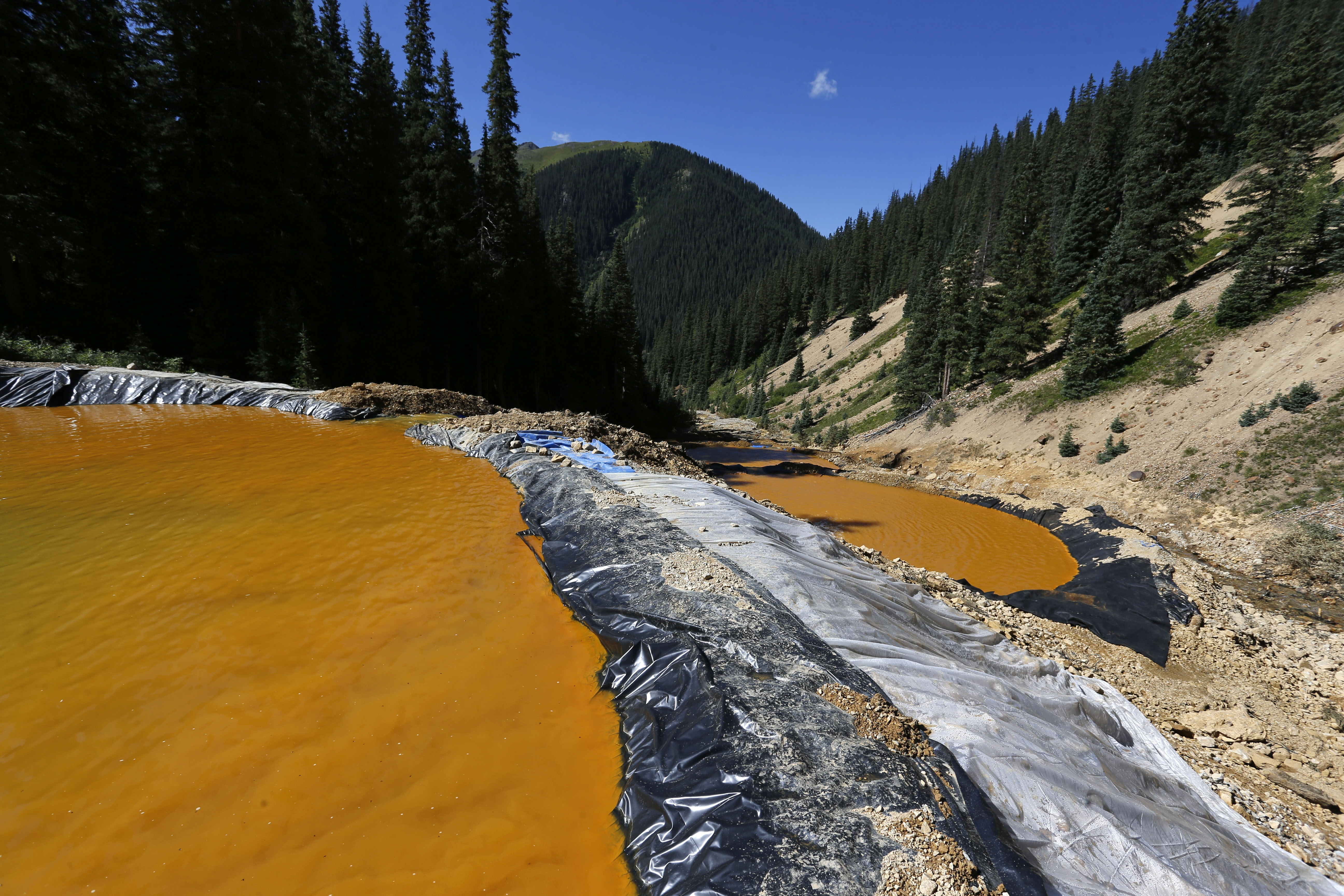20150814 In this Aug. 14, 2015, photo, water flows through a series of sediment retention ponds built to reduce heavy metal and chemical contaminants from the Gold King Mine wastewater accident, in the spillway about 1/4 mile downstream from the mine, outside Silverton, Colo. Colorado officials are disputing a key claim by federal agencies about a massive spill of toxic wastewater from an inactive mine.