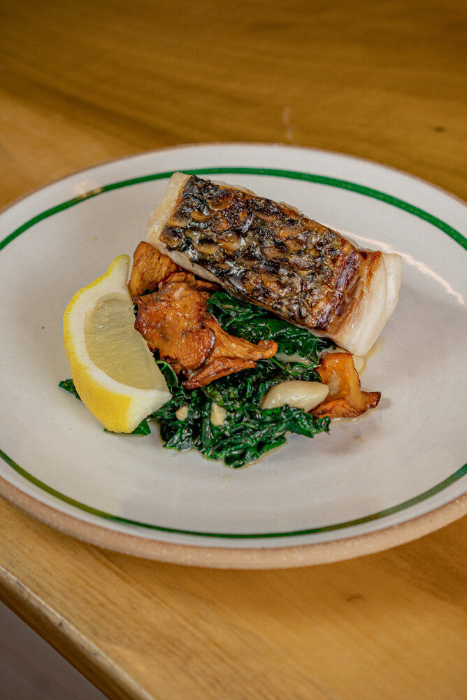 A piece of fish sits a top a bed of cooked vegetables, accompanied by a lemon wedge, on a white plate.