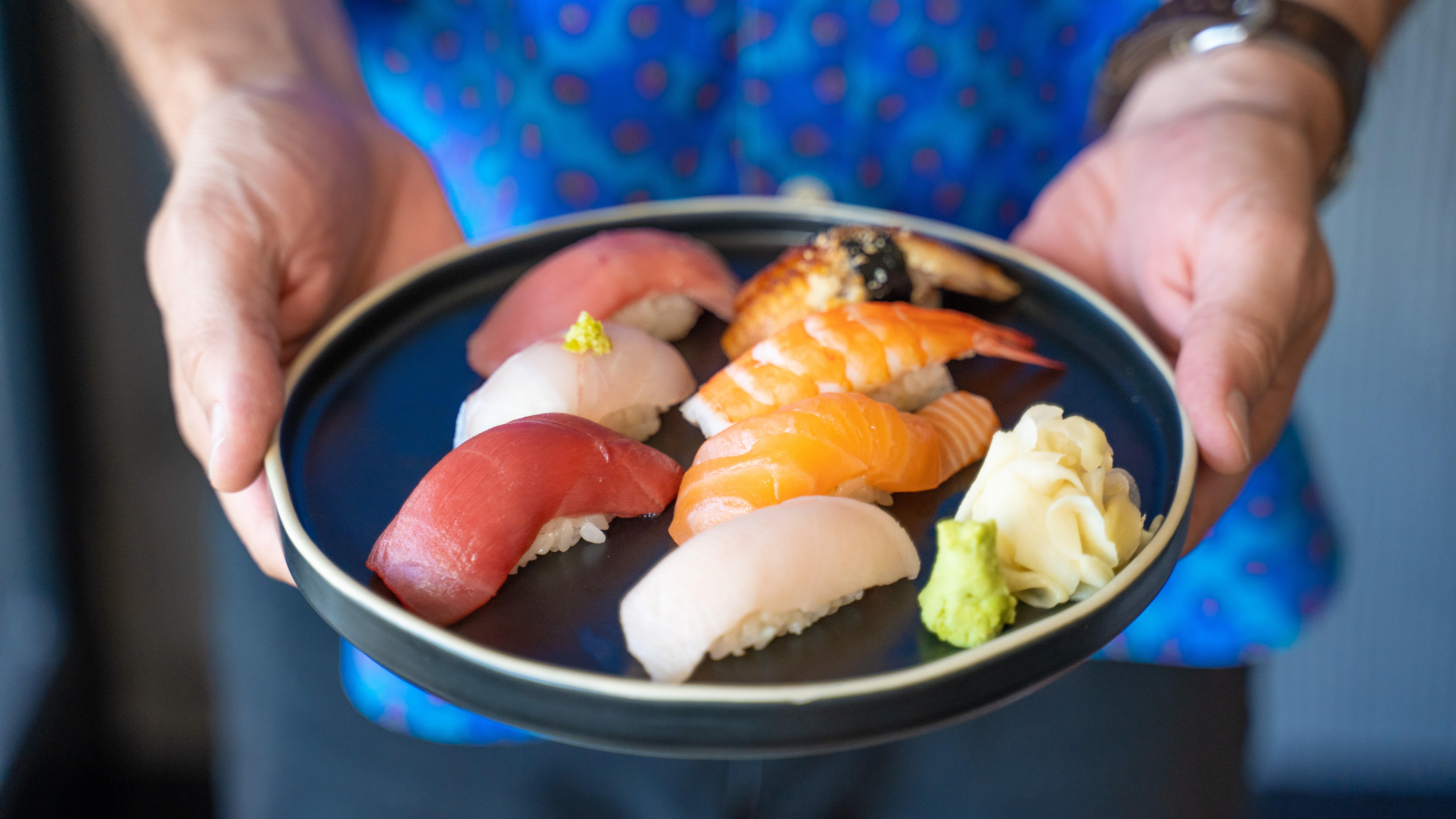 Two hands hold a plate of nigiri sushi, ready for service.