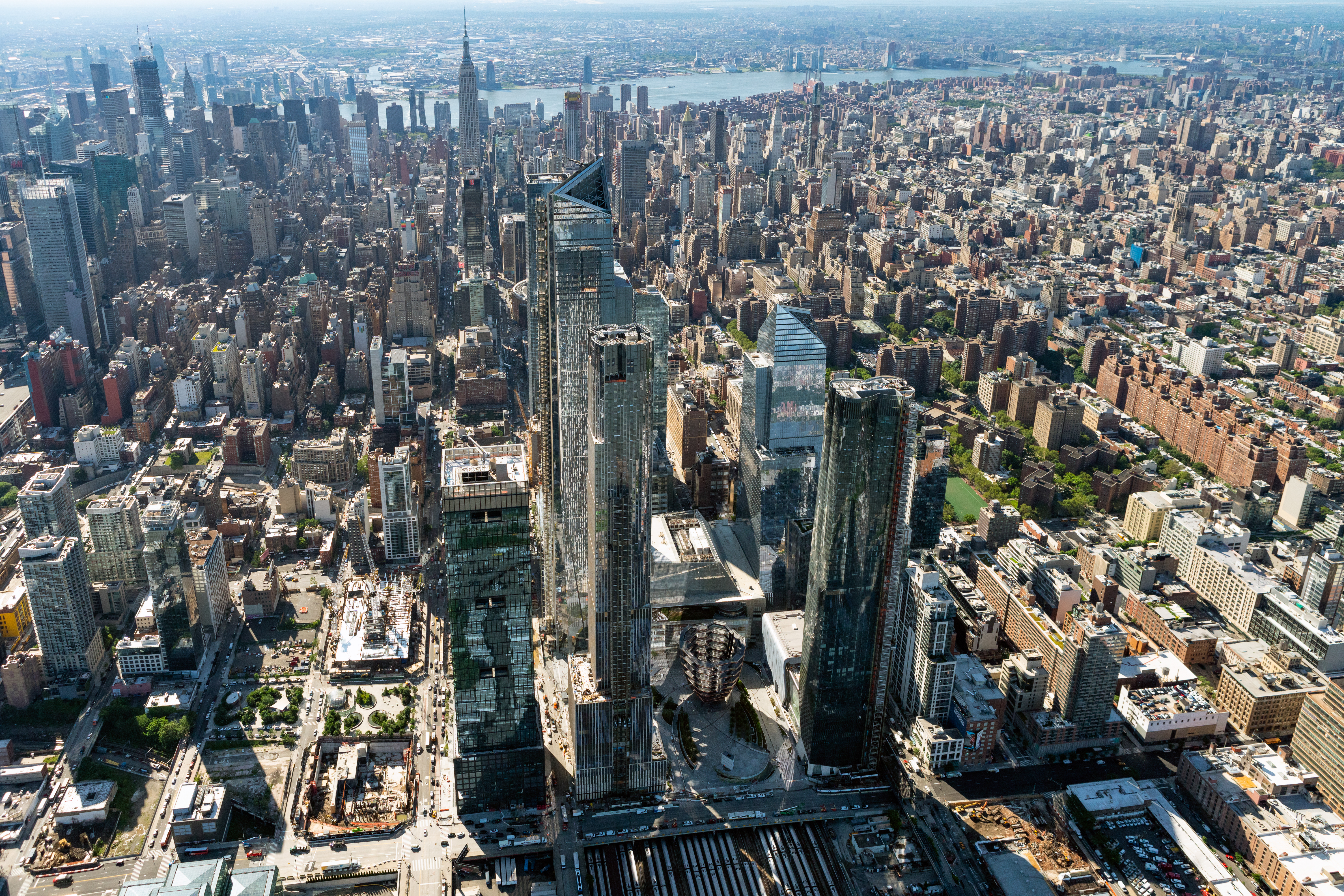 An aerial view of Manhattan, with Hudson Yards and the Empire State Building in sight, for an article that talks about NYC real estate and the Manhattan housing market.