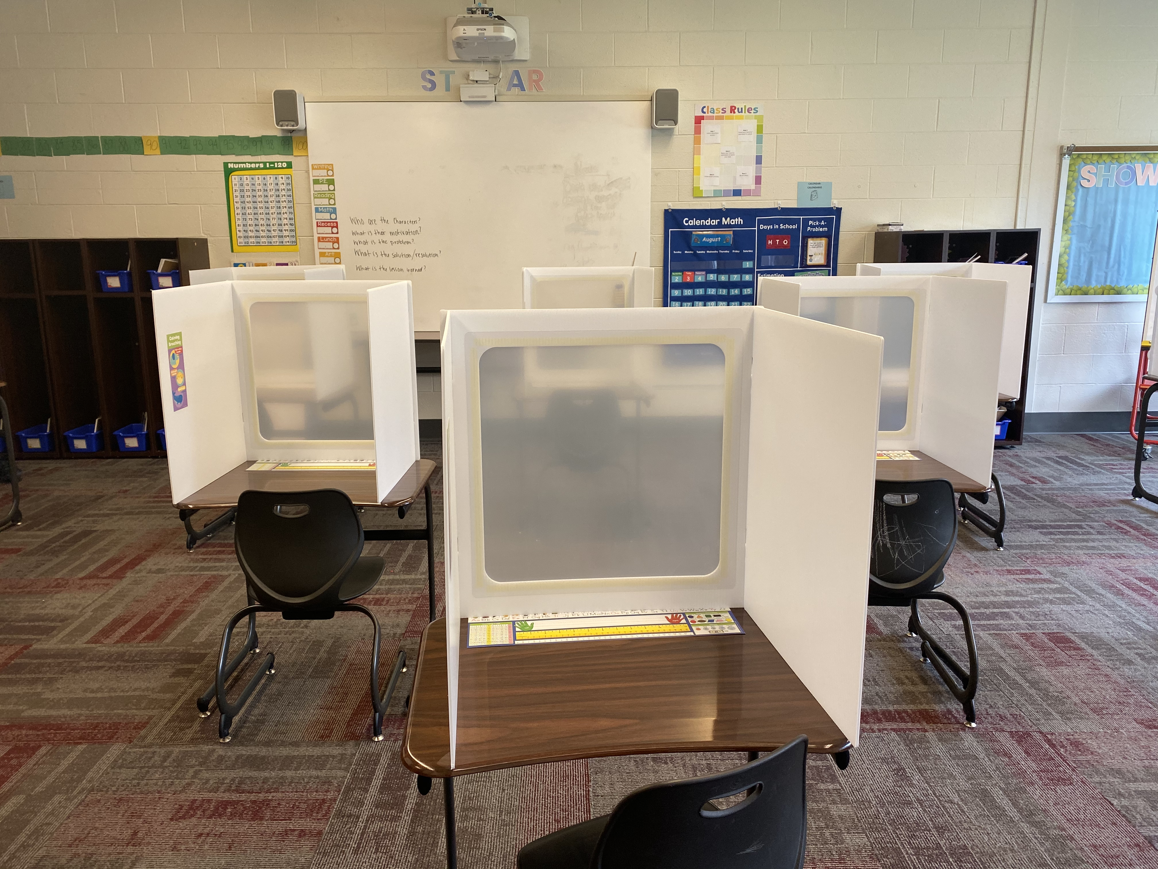 In a first-grade classroom at Tindley Summit Academy in Indianapolis, empty desks sit spaced out in rows with plastic shield dividers so students can take off their masks while working.