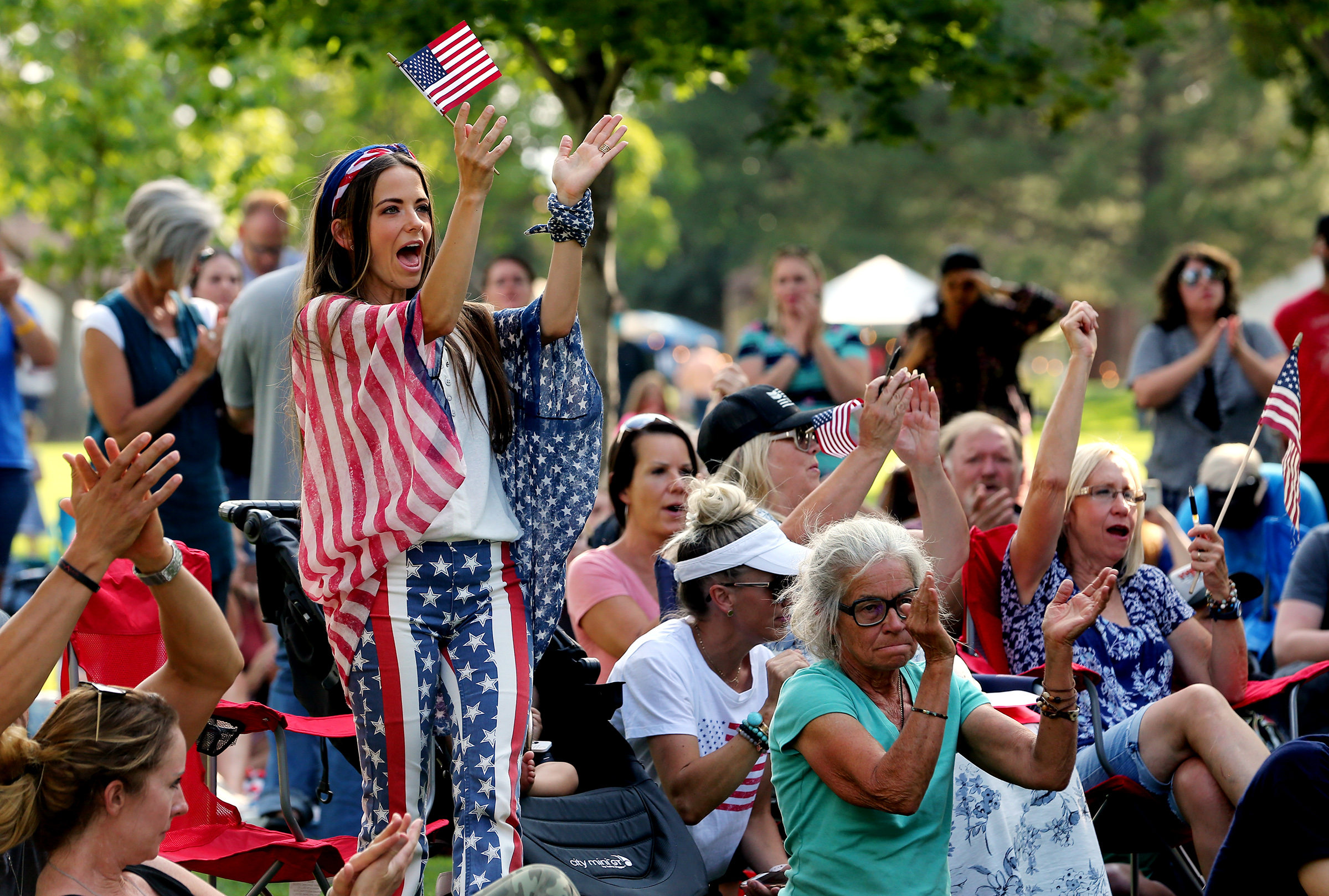 Angelique Davis Farnes stands and cheers as she and other protesters gather in the City Center Park of Orem in opposition to mask mandates on Wednesday, Aug. 5, 2020.