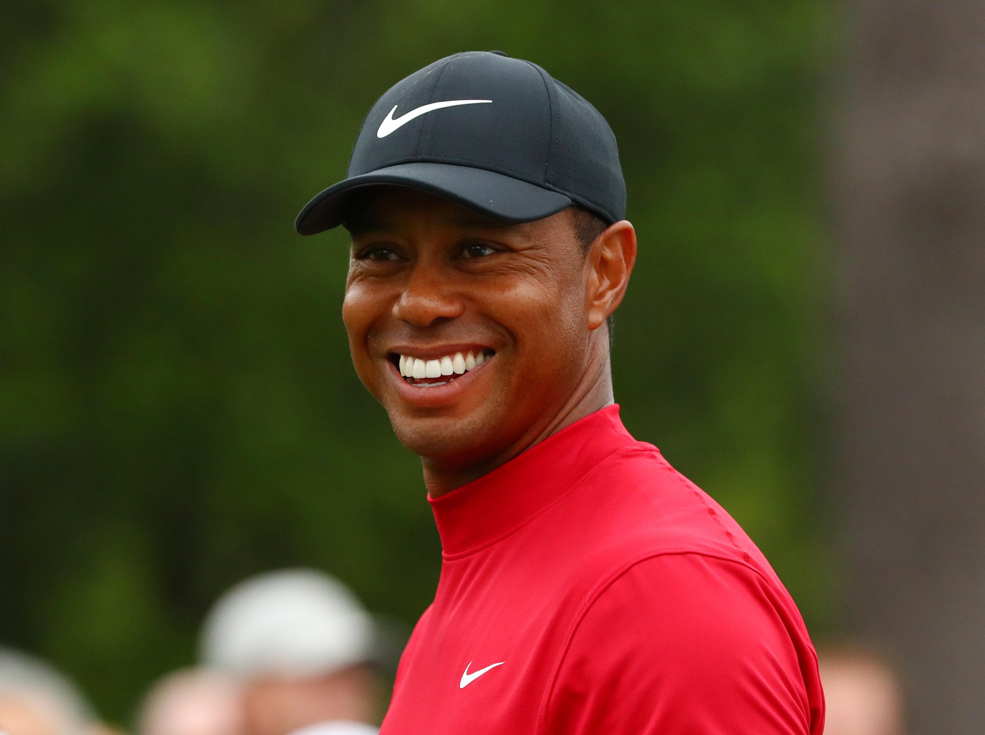 在奥古斯塔国家高尔夫俱乐部举行的美国高尔夫大师赛的最后一轮比赛中,老虎伍兹微笑着走下第8个球座。