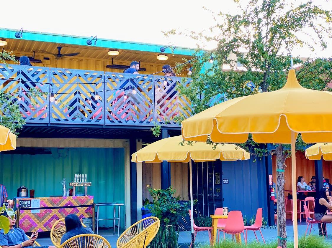 A colorful all-outdoor beer garden hangout with yellow umbrellas.