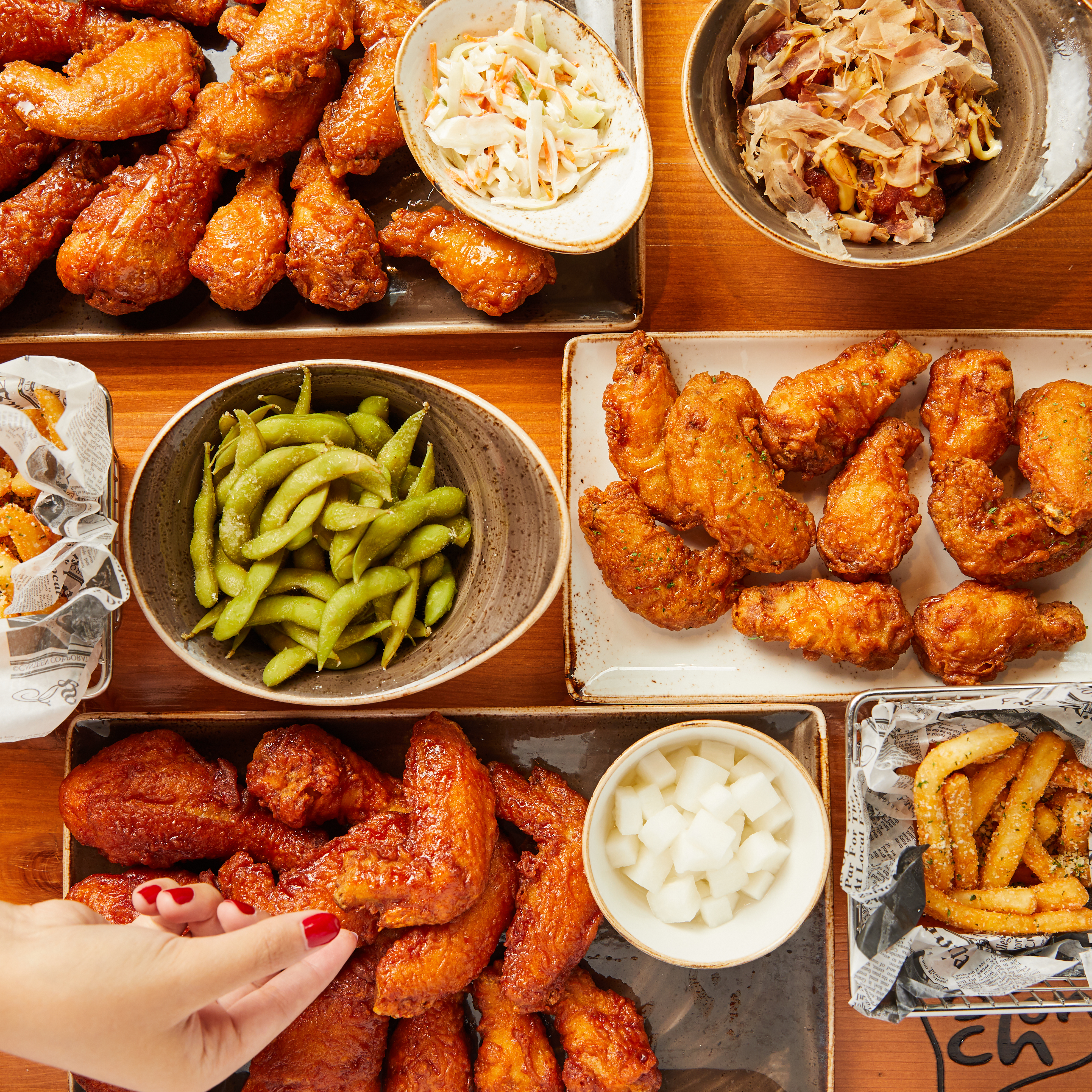 A wooden table is covered in plates of fried chicken, edamame, fries, and radish