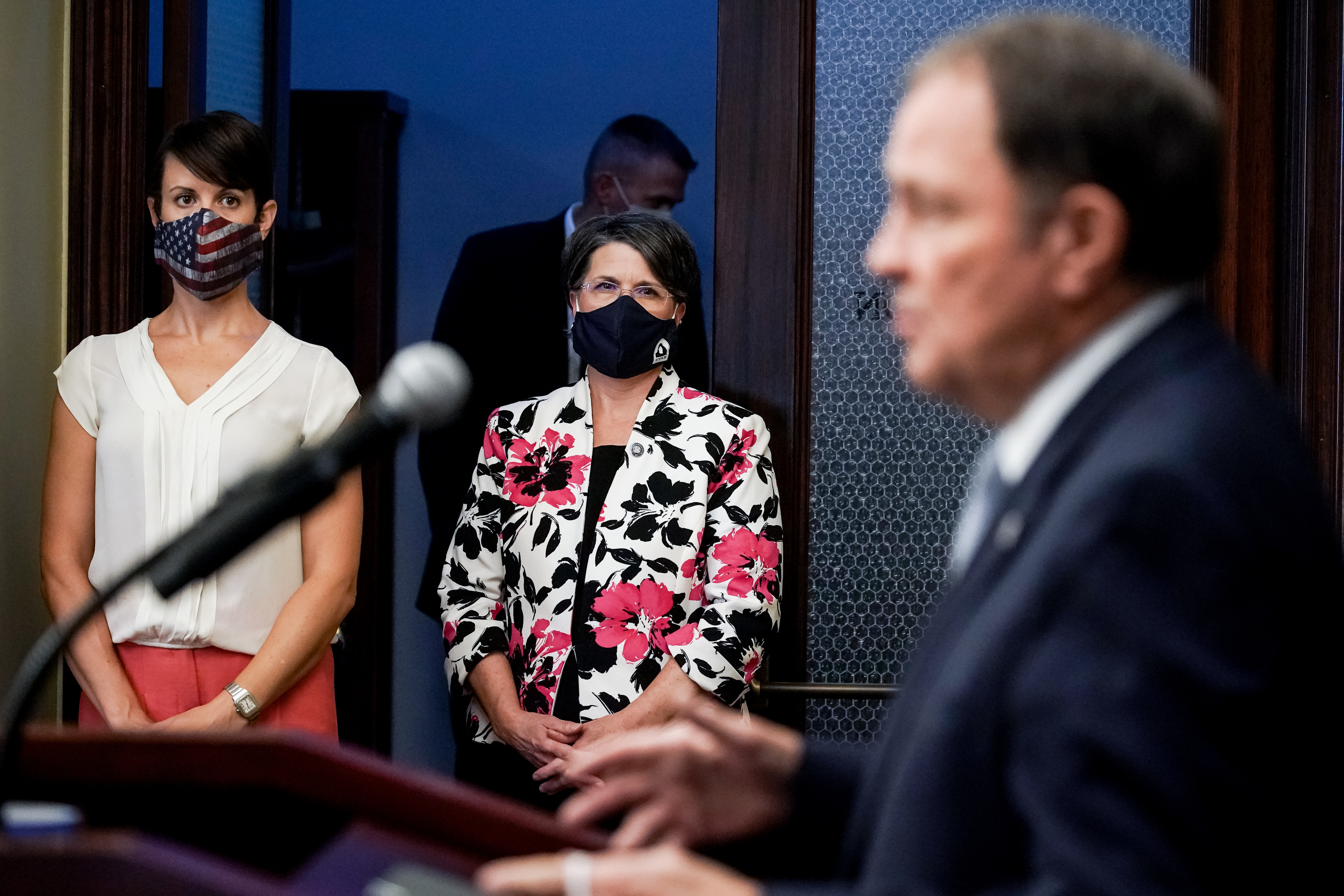 State epidemiologist Dr. Angela Dunn, left, and Tami Pyfer, education adviser to Gov. Gary Herbert, center, listen as Herbert speaks during a briefing about the state's response to the COVID-19 pandemic at the Capitol in Salt Lake City on Thursday, Aug. 6, 2020.