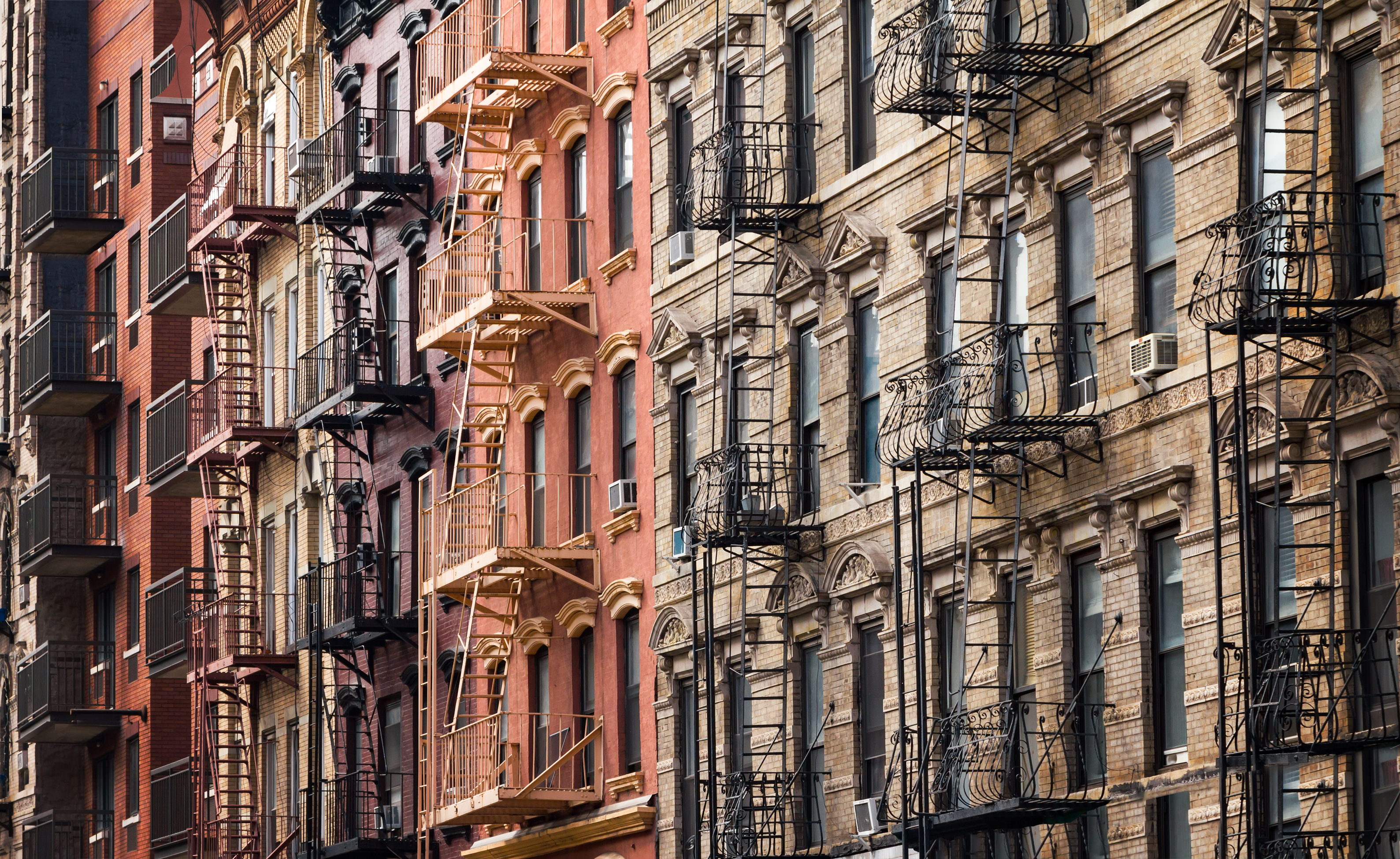 A close-up view of a row of apartment buildings with fire escapes.