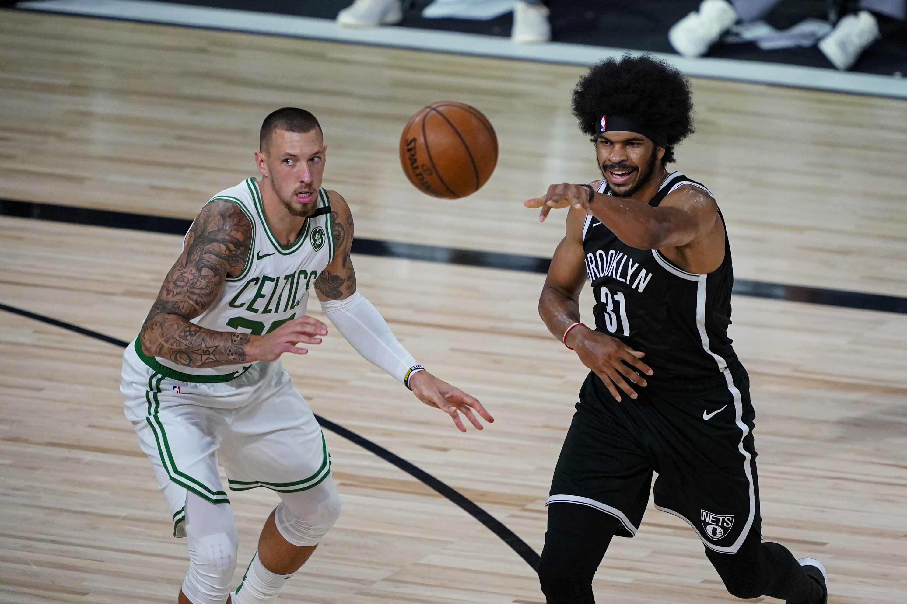 Jarrett Allen of the Brooklyn Nets passes around Daniel Theis of the Boston Celtics during the first half of an NBA basketball game at the ESPN Wide World Of Sports Complex on August 5, 2020 in Lake Buena Vista, Florida.