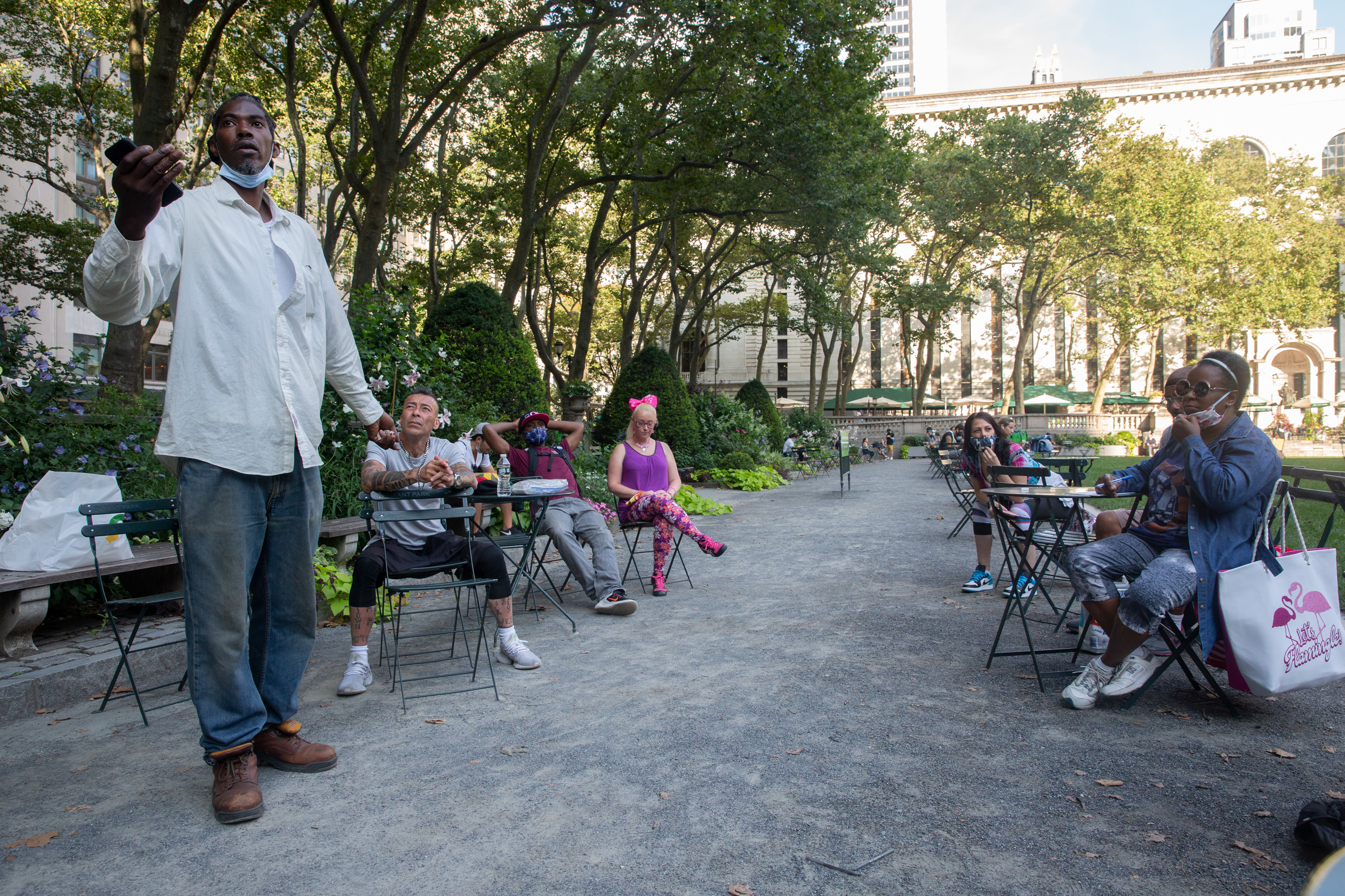 Marcus Moore, left, speaks to a group of fellow homeless people in Bryant Park about how to pressure the city to pay for hotel rooms they've been staying in during the pandemic, on July 15, 2020.