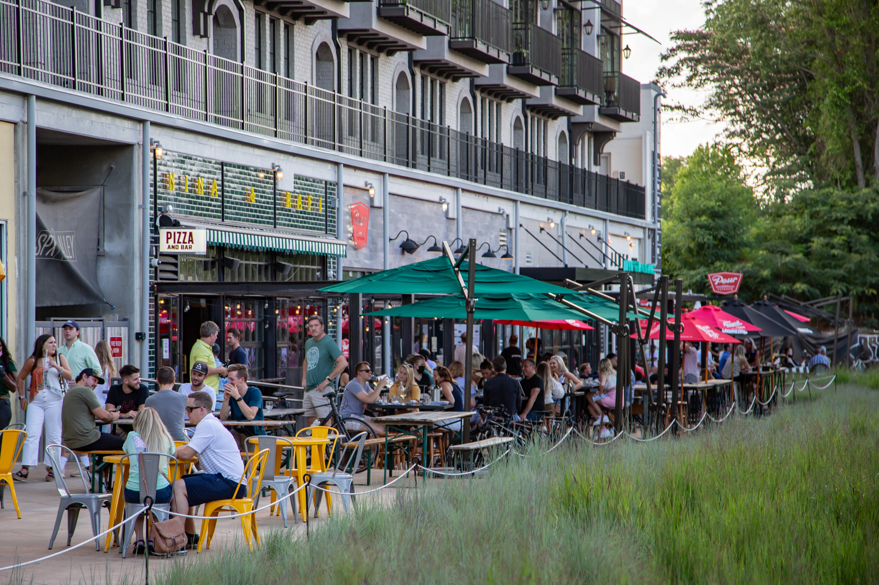 Diners eating on restaurant patios in the late afternoon in June 2020 at SPX Alley on the Eastside Beltline in Atlanta