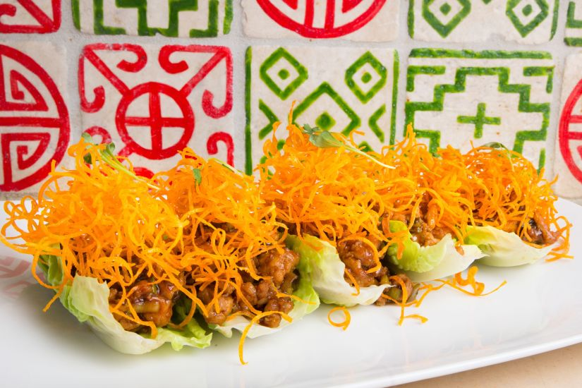 Five chicken dishes on a lettuce cup with red and green tile behind