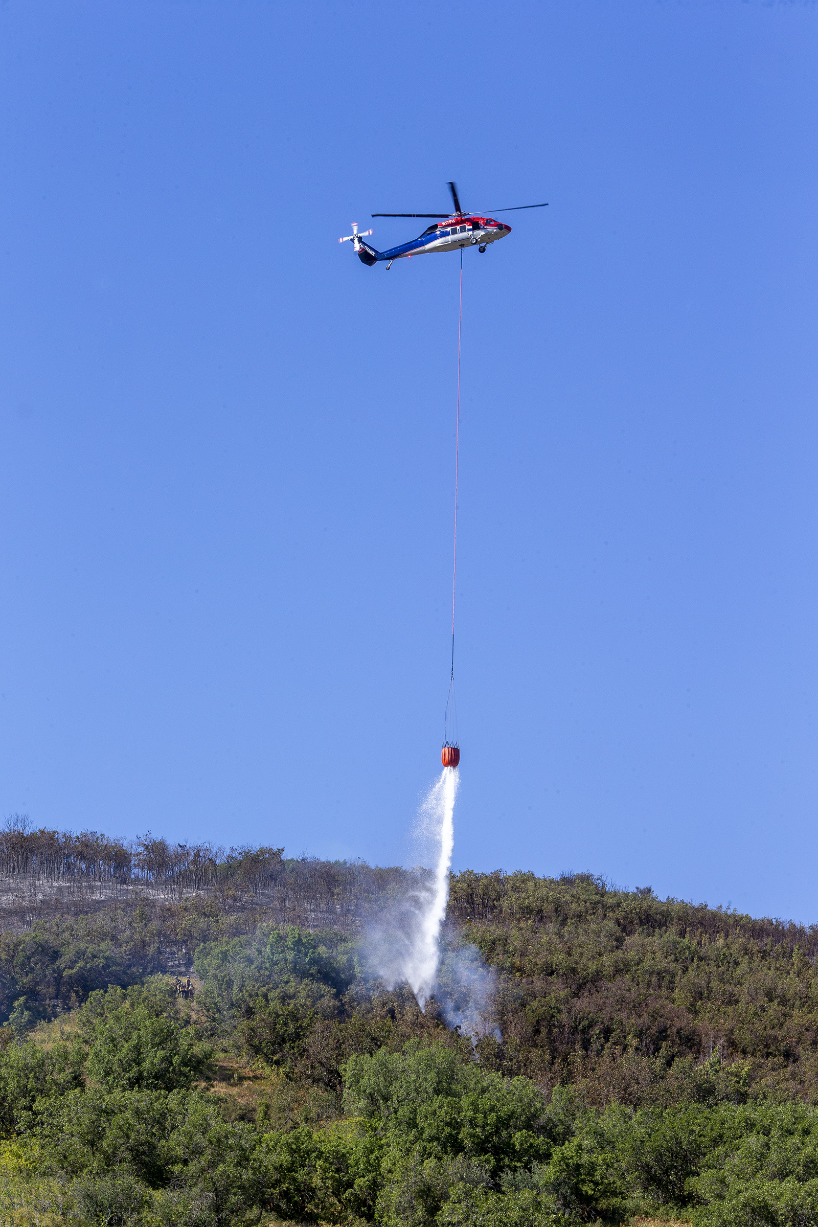 A helicopter drops water on a small smoke plume as firefighters battle a fire in Parleys Canyon east of Salt Lake City on Friday, Aug. 7, 2020.