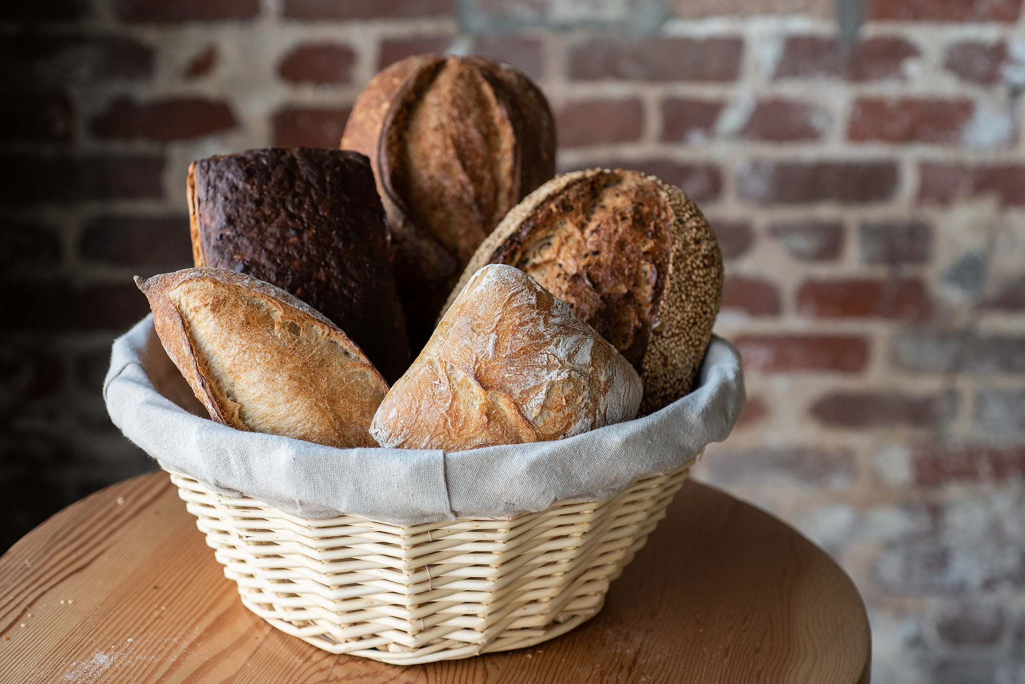 A basket of freshly baked breads on varying sizes.