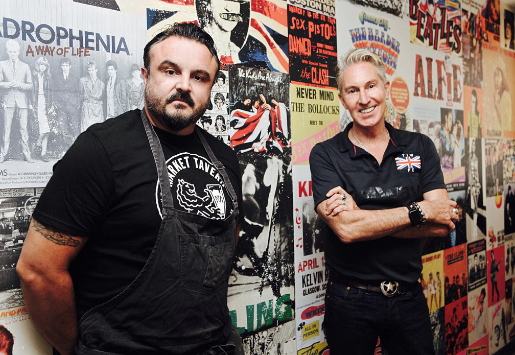 Two chefs stand side by side along a graffitied wall.