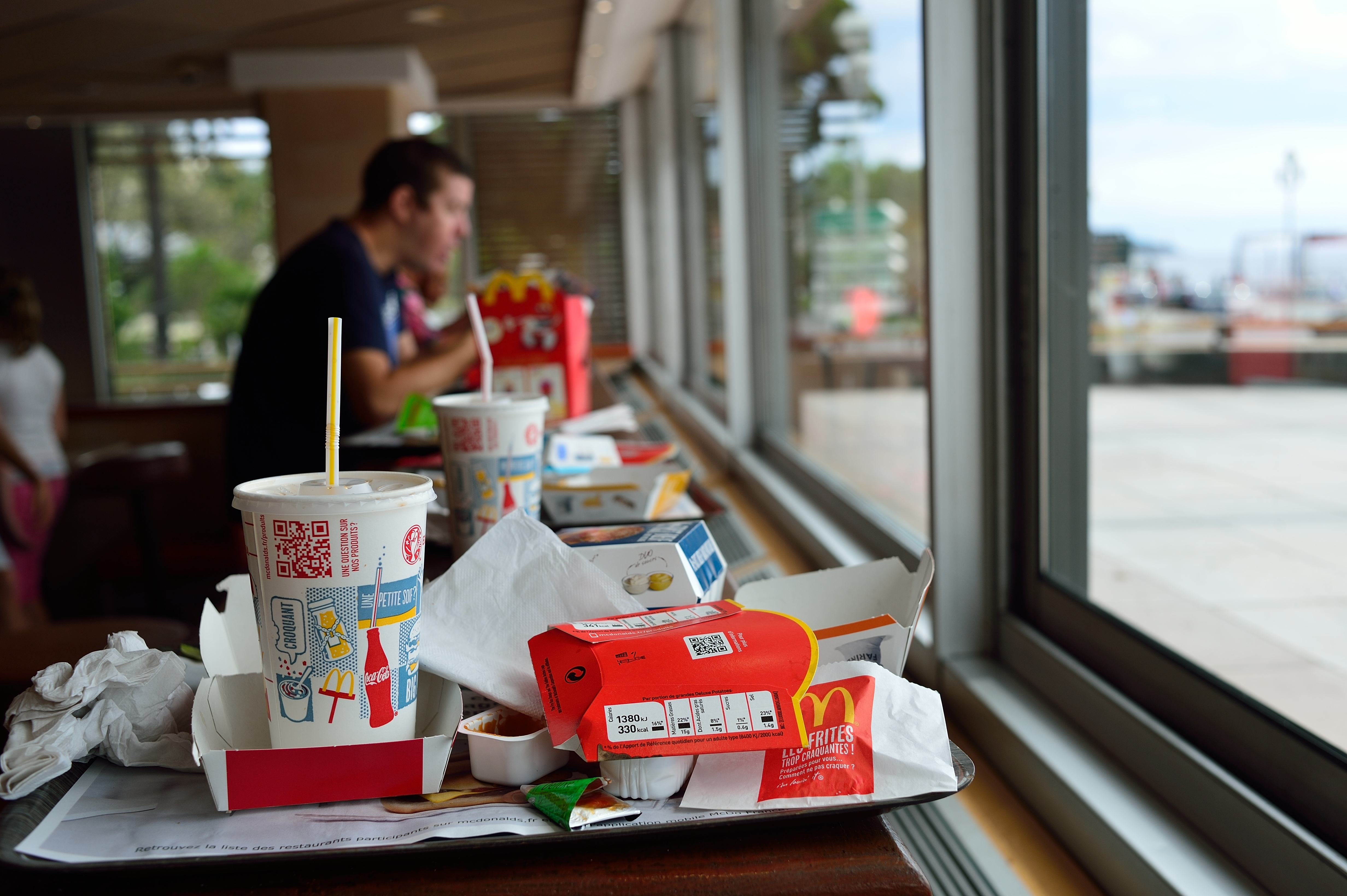 A brown tray full of used and crumpled McDonald's wrappers and cups is left on a window-facing counter top with a diner obscured in the background.