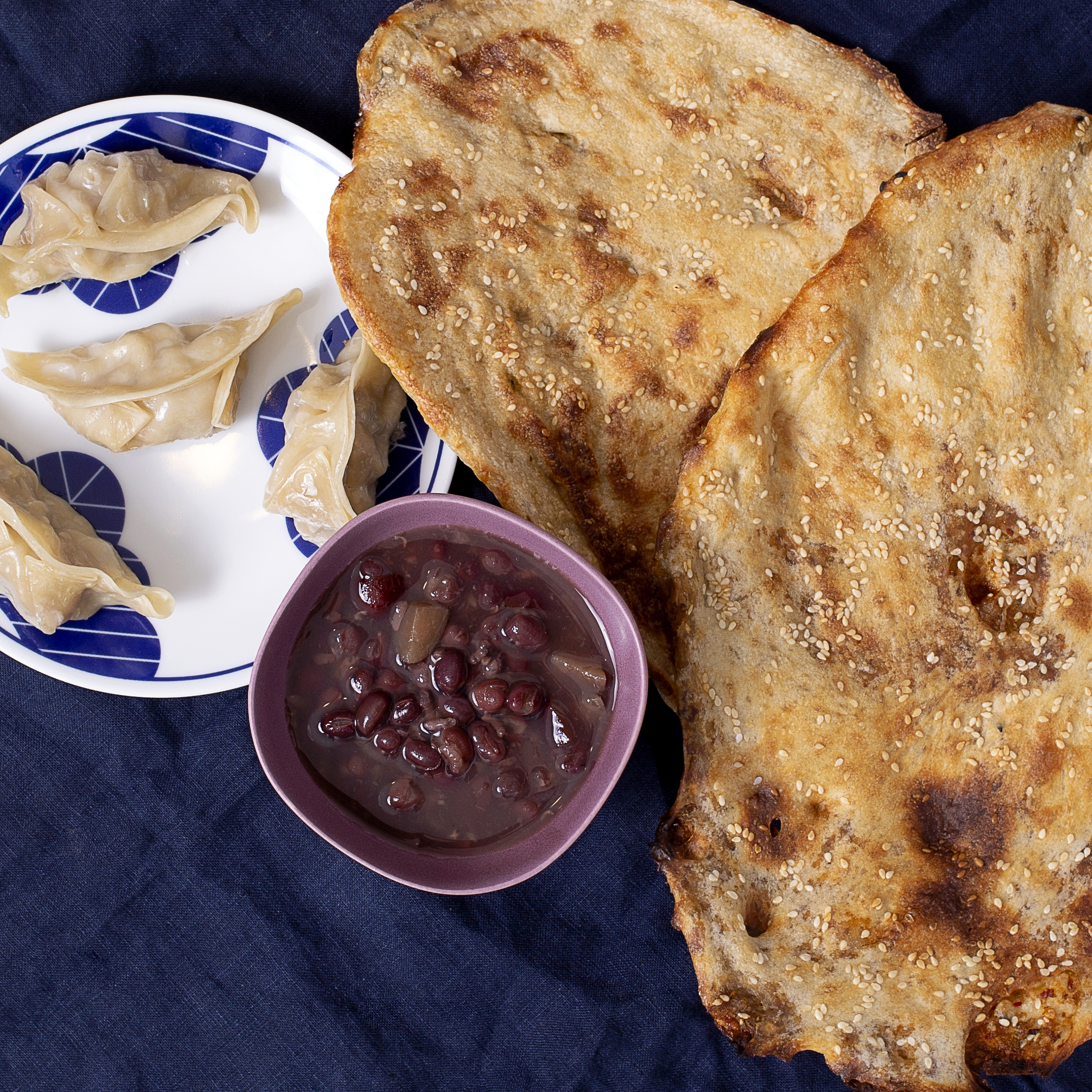 Two toasted flat breads pictured with a cup of soup and four steamed dumplings on a plate
