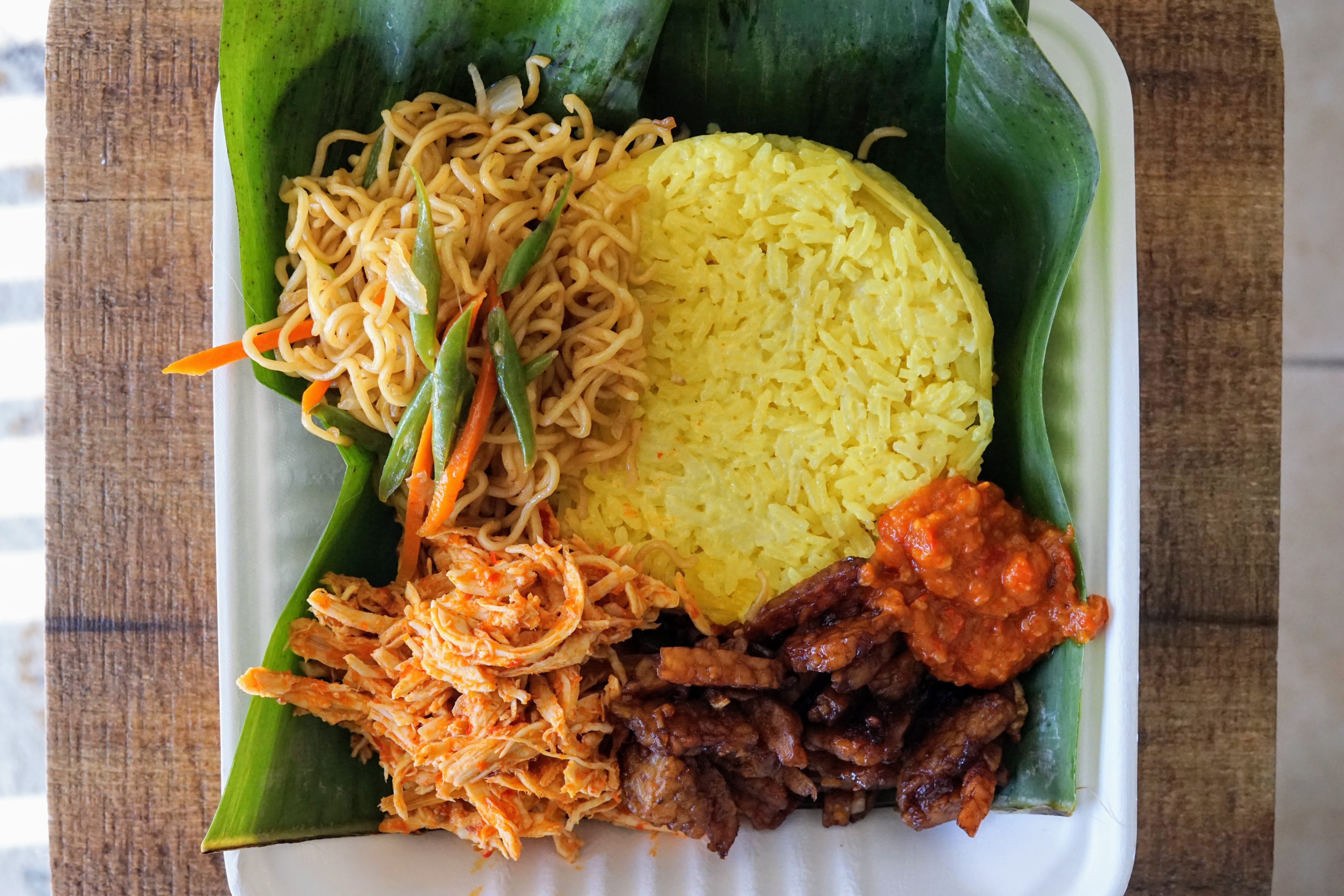 Nasi jinggo, a classic Balinese dish with chicken and yellow rice cooked in turmeric and coconut milk, from Bali Mesari.