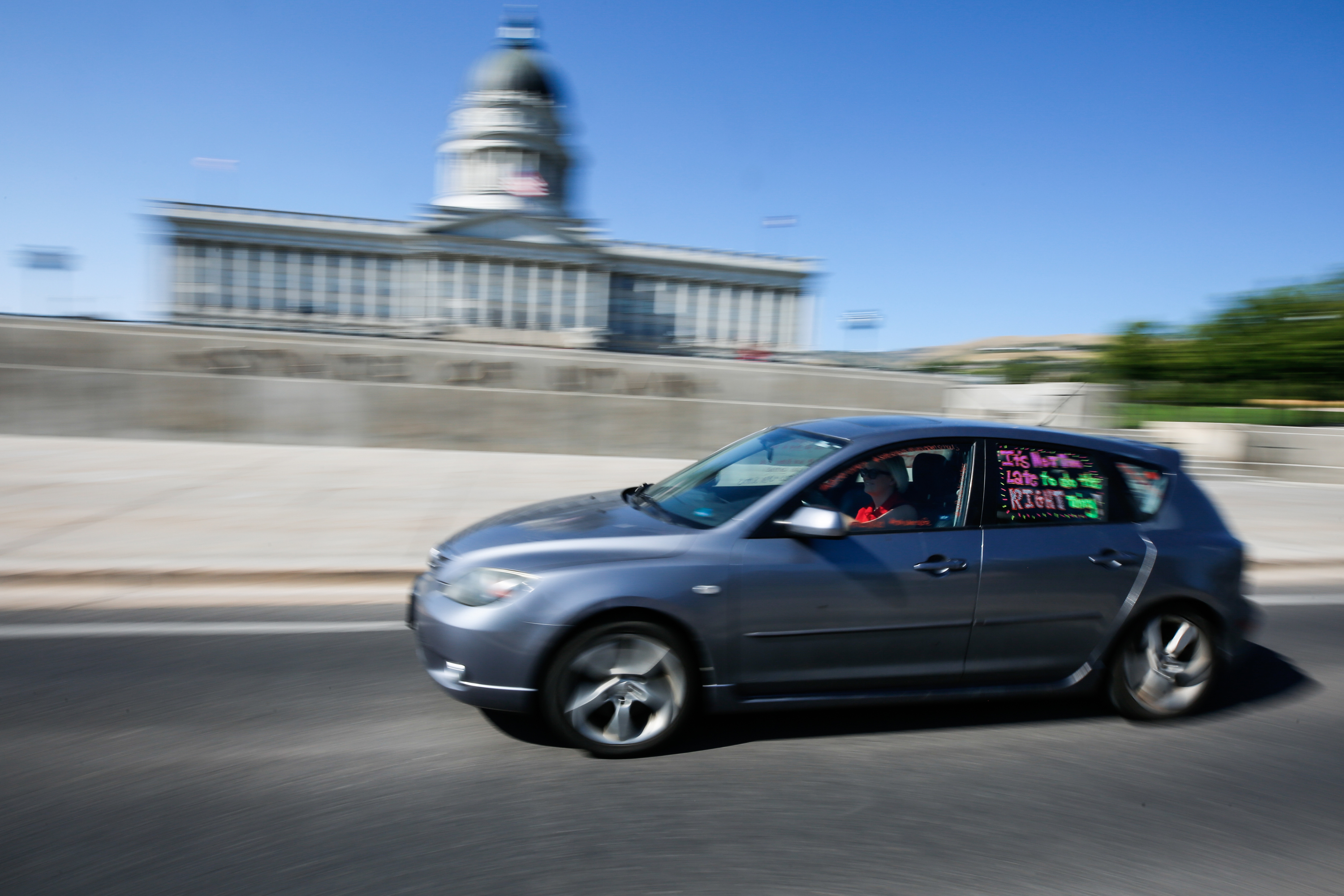 A car painted with slogans drives past the Capitol during a caravan-style rally to show support for opening schools safely in Salt Lake City on Friday, Aug. 7, 2020.